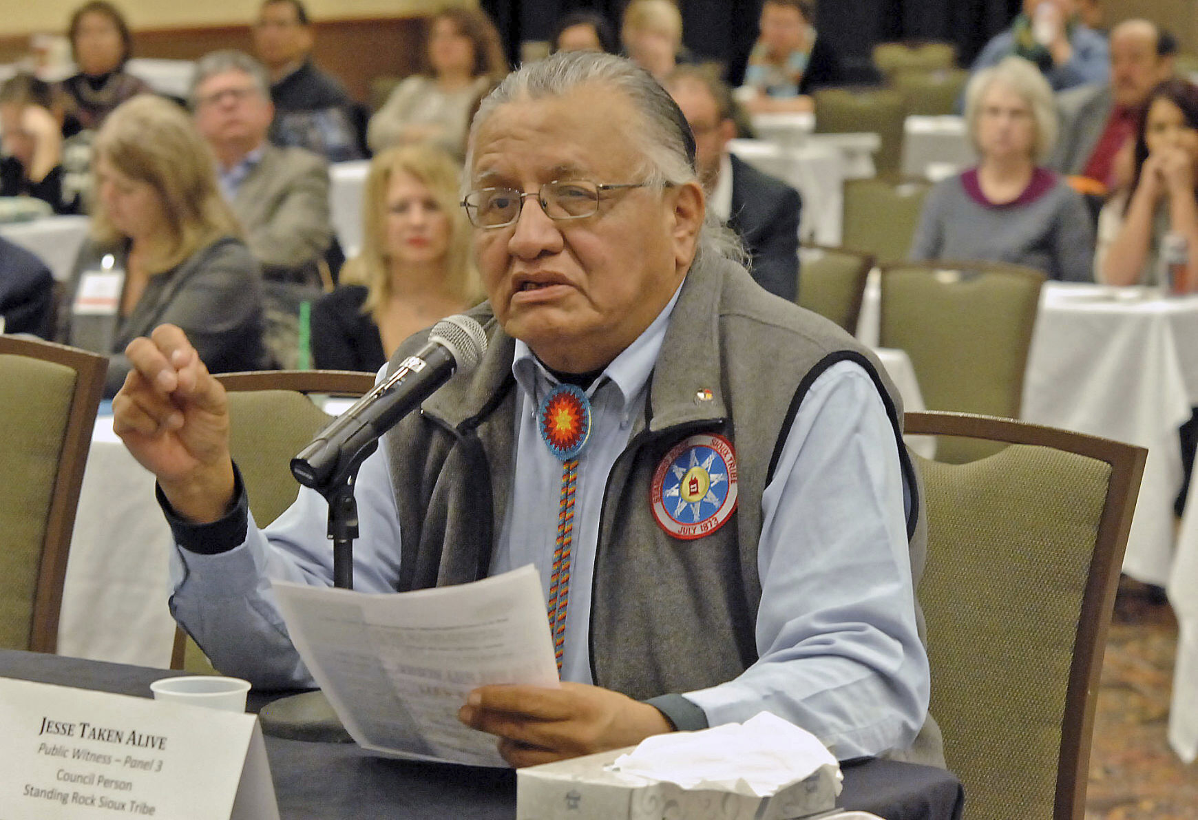 This 2013 file photo shows Jesse Taken Alive of the Standing Rock Sioux Tribe testifying in Bismarck, N.D. Family members say the former chairman of the Standing Rock Sioux Tribe died in December after contracting COVID-19, not long after his wife passed away from the coronavirus. He taught Lakota culture and language at a school in his hometown of McLaughlin, South Dakota.