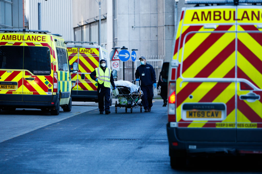 Medical staff wheel a patient on a stretcher to an ambulance outside the emergency department of the Royal London Hospital in London, England, on January 25, 2021.