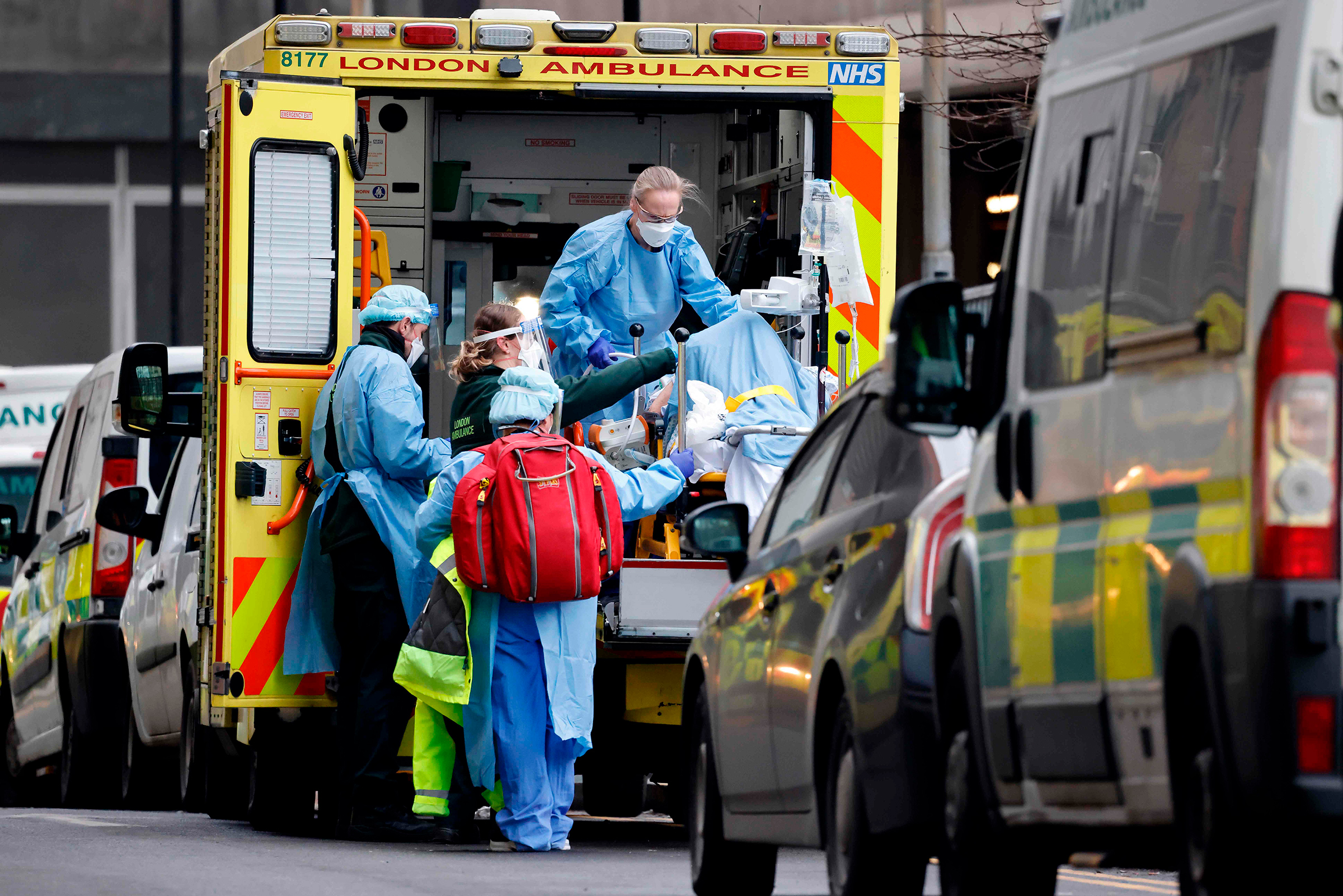 A patient is taken from an ambulance by staff wearing PPE equipment at the Royal Free Hospital, London, on Jan. 11 as surging cases of Covid-19 are placing health services under increasing pressure