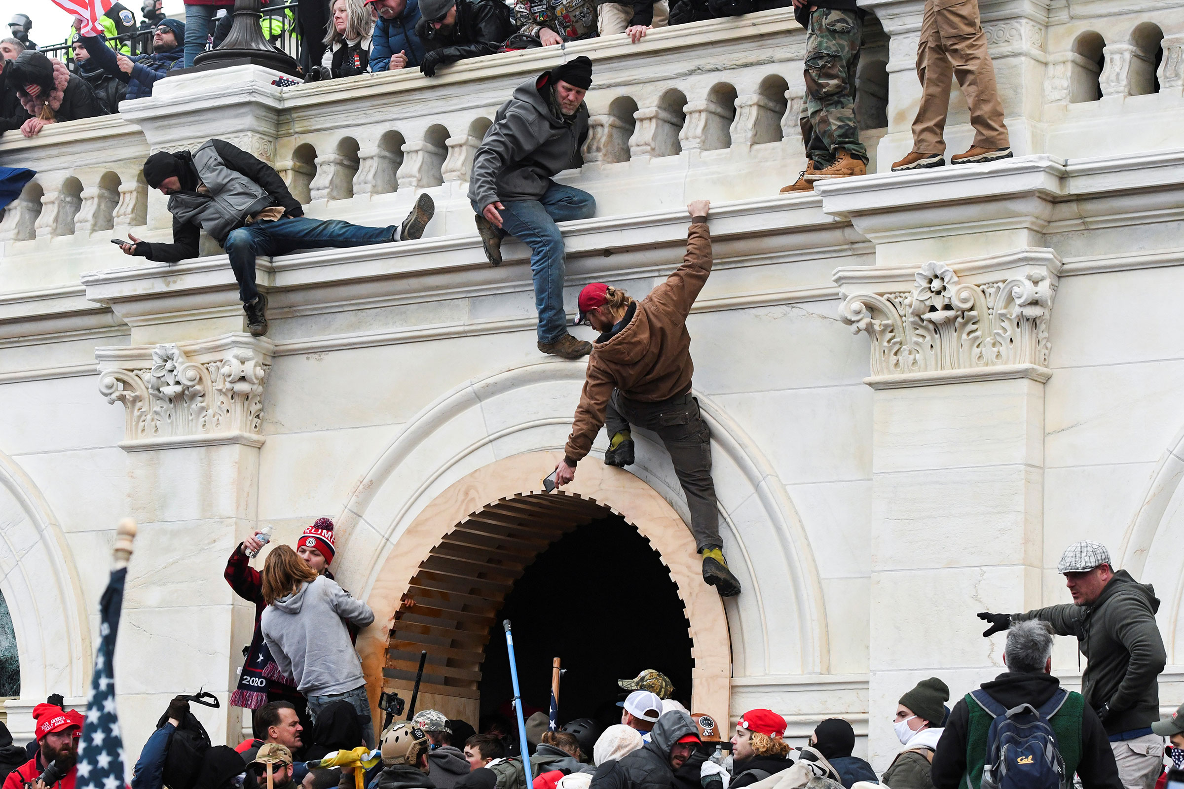 Rioters climb the walls of the U.S. Capitol after President Trump encouraged a rally audience to pressure Republican lawmakers.