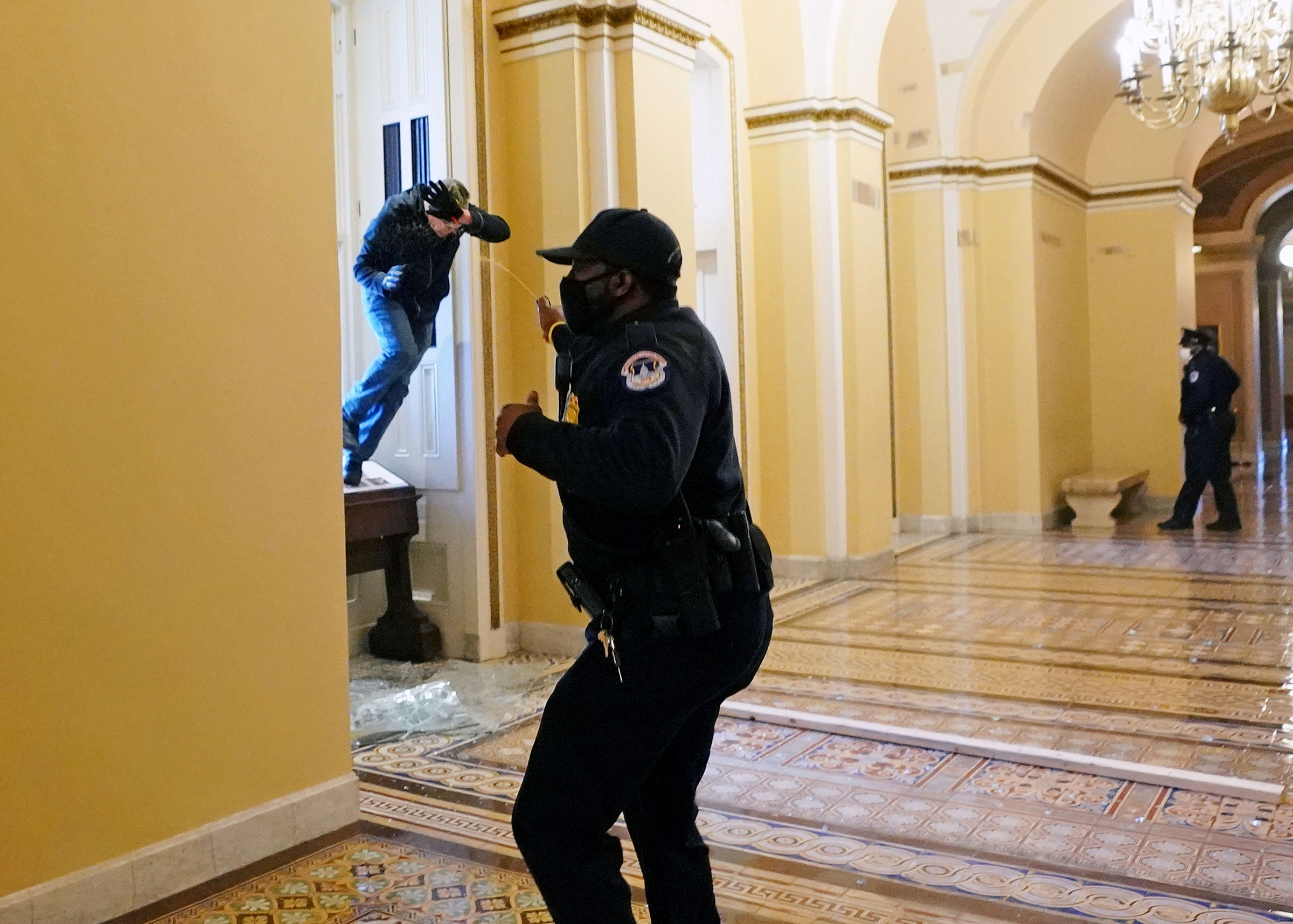 A Capitol police officer confronts a Trump supporter scrambling into the Capitol through a smashed window.