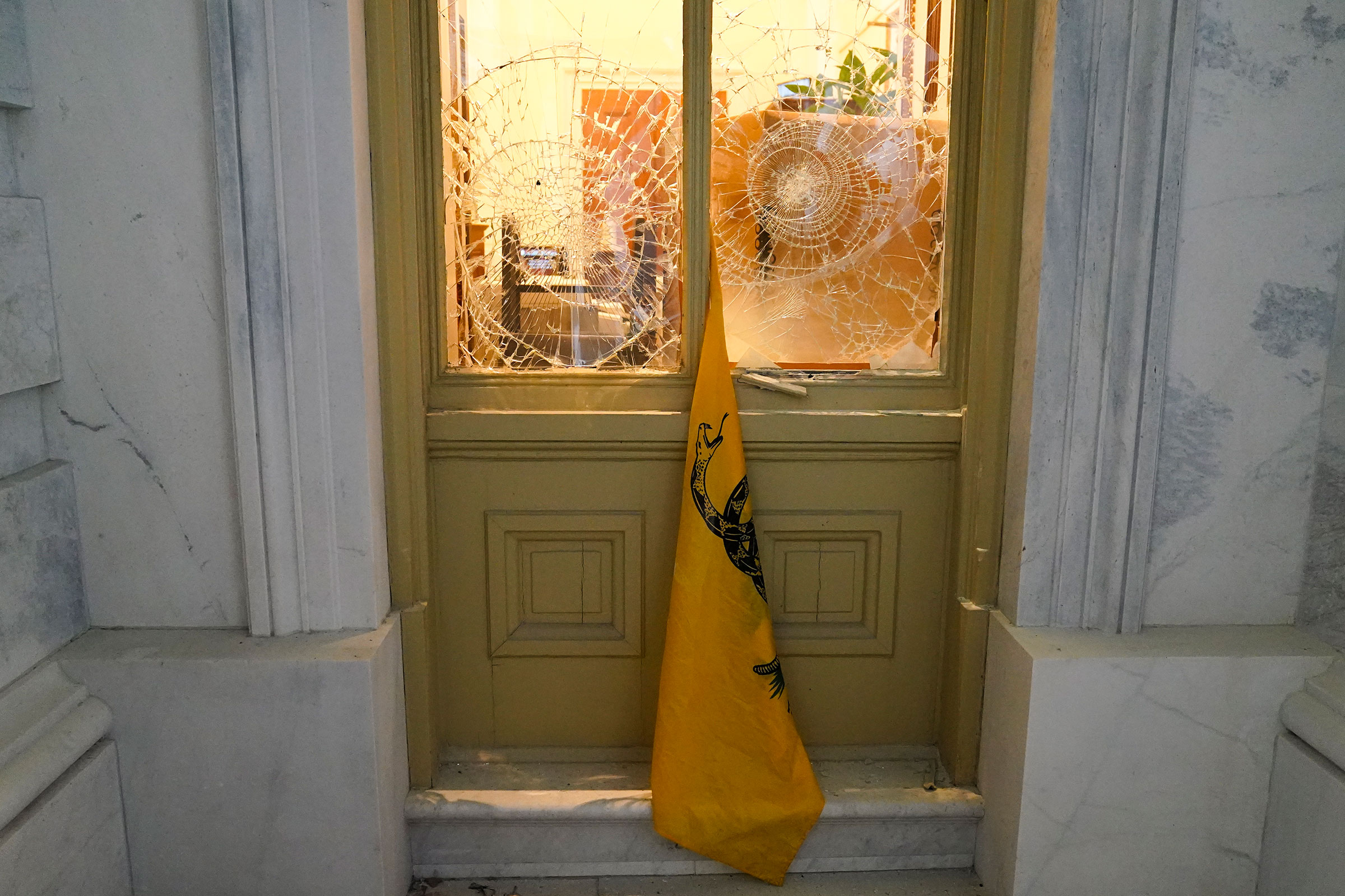 A flag hangs between broken windows after supporters of President Donald Trump tried to break through police barriers outside the Capitol on Jan 6.
