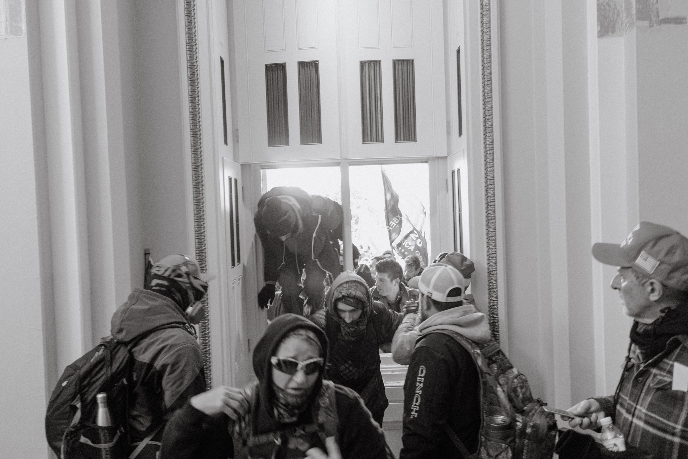 Pro-Trump rioters enter the Capitol through a broken window.