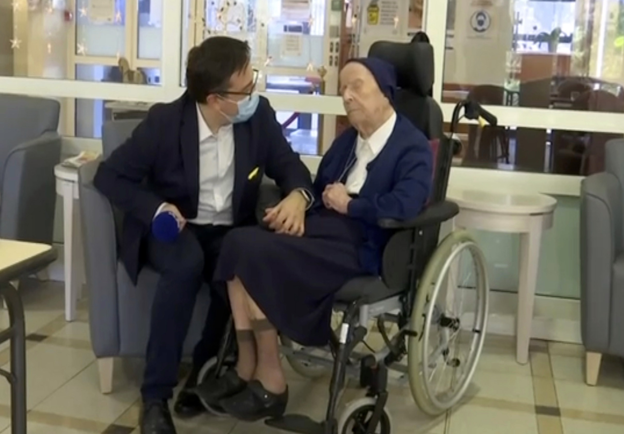 In this image made from BFM TV video, Sister Andre, born Lucile Randon, is interviewed by David Tavella, Communications Manager for the Sainte Catherine Laboure Nursing Home in Toulon, France, Tuesday Feb. 9, 2021.