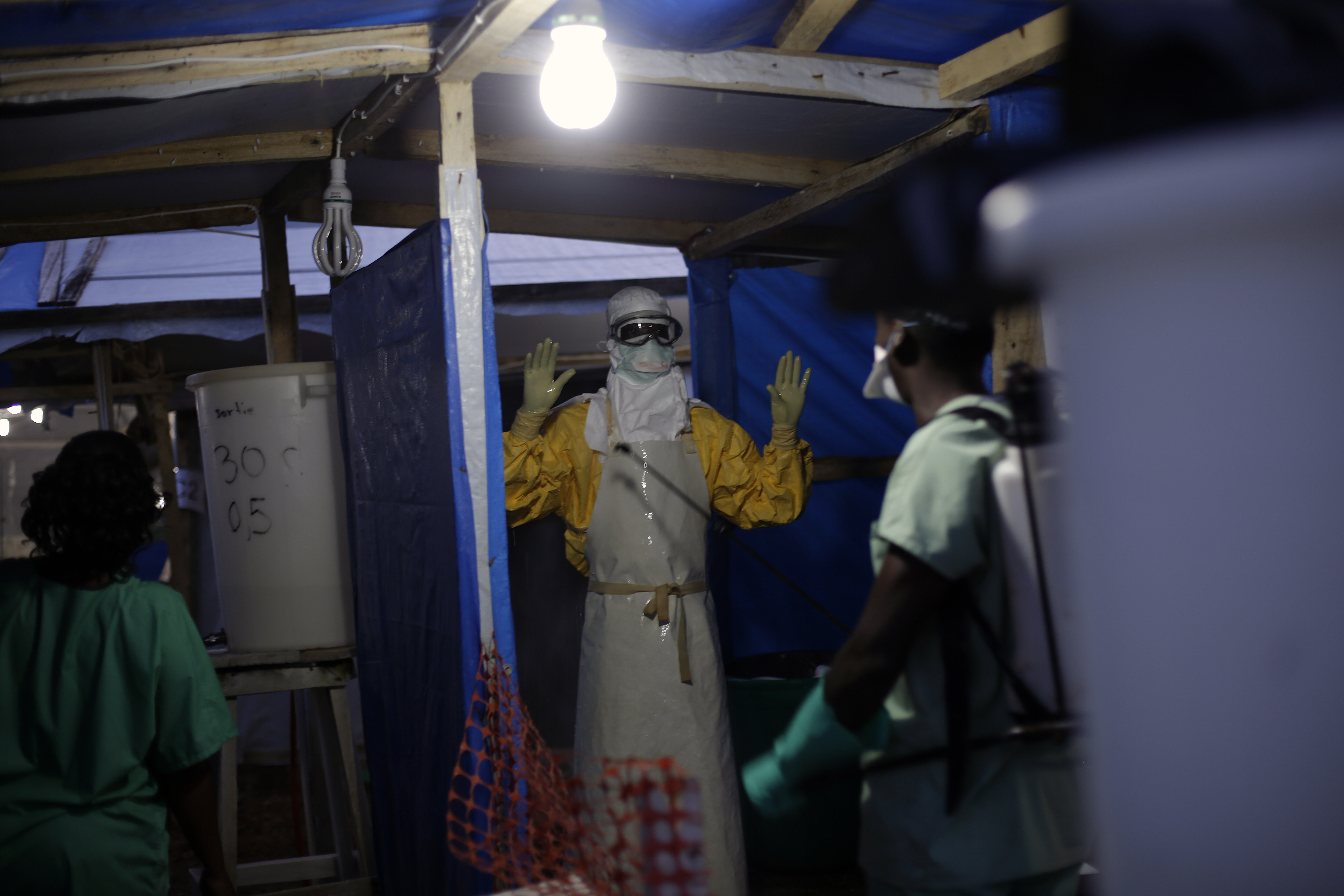 An MSF Ebola heath worker is sprayed as he leaves the contaminated zone at the Ebola treatment centre in Gueckedou, Guinea, on Nov. 20, 2014.
