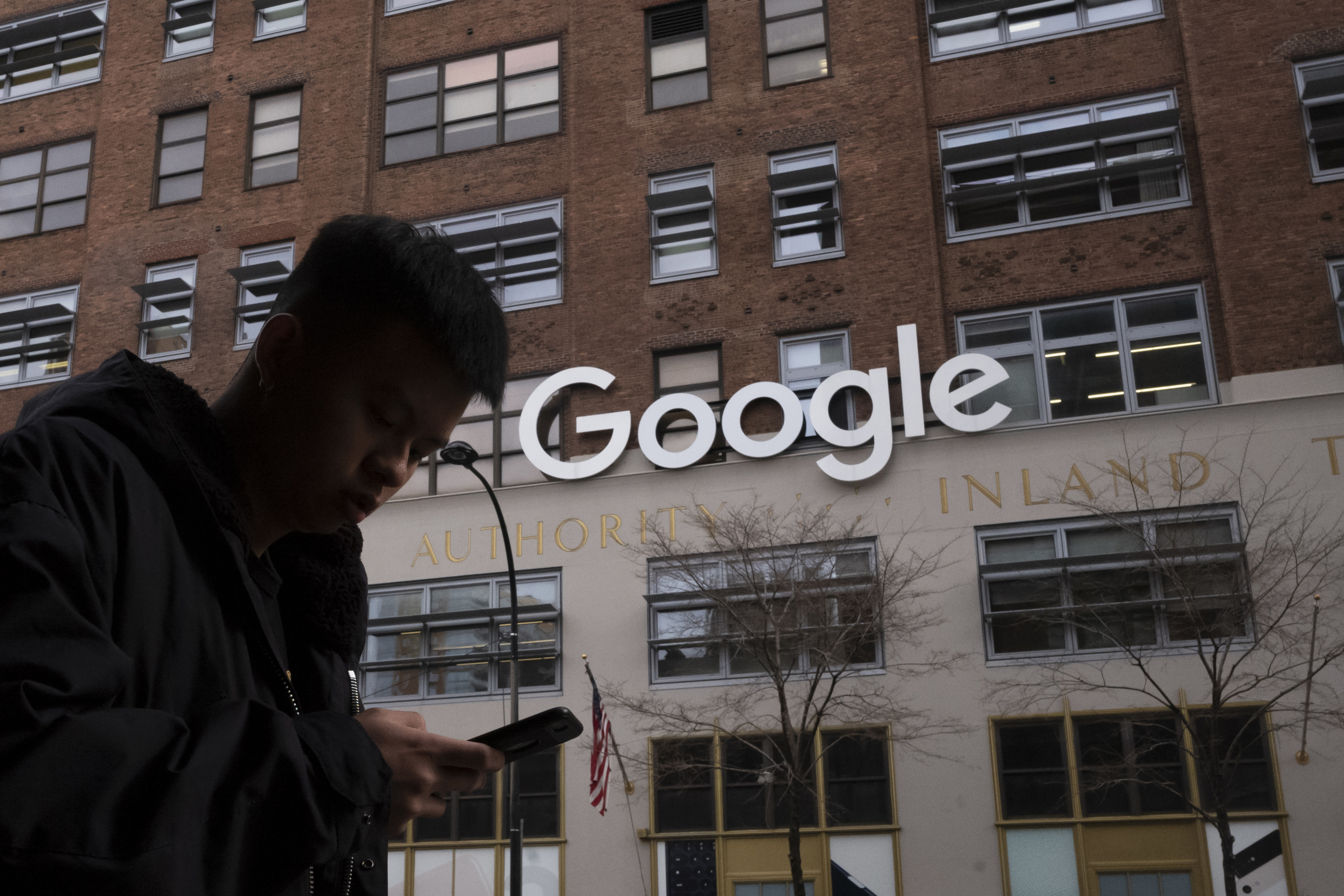 In this Dec. 17, 2018, file photo a man using a mobile phone walks past Google offices in New York.