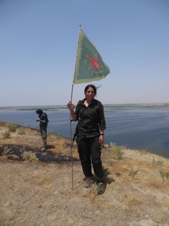 Azeema standing with flag in the Kobani countryside, January 2015