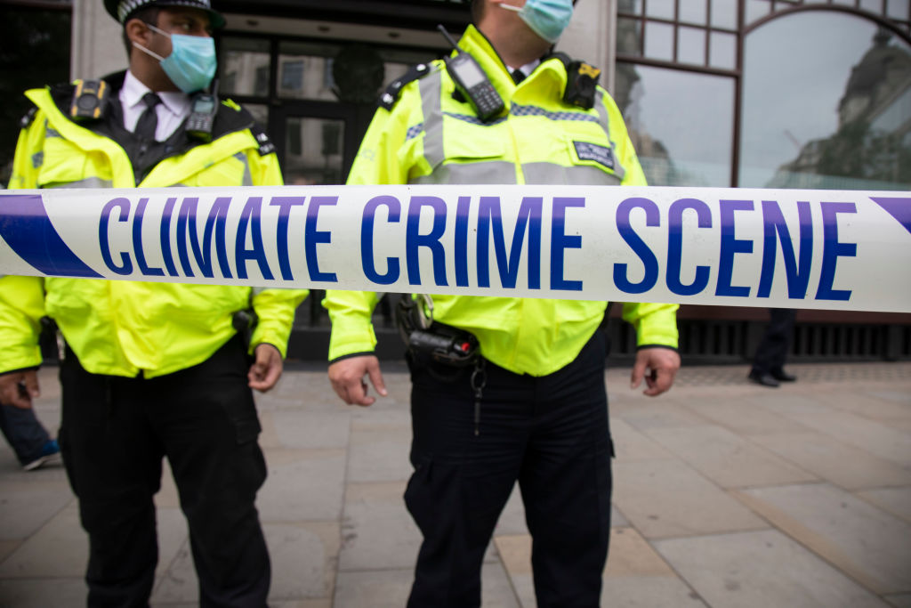 Police watch as Extinction Rebellion  crime scene investigators  in white suits and masks put up climate crime scene tape to investigate areas of ecocide in a performance outside the Brazilian Embassy on Sept. 7, 2020 in London, United Kingdom