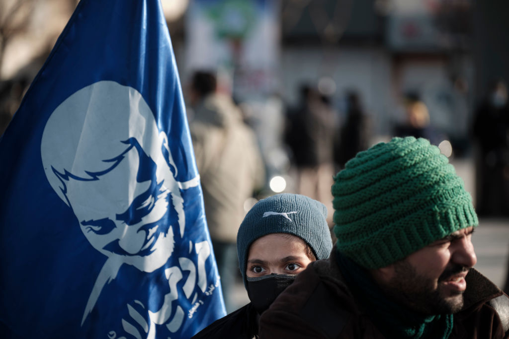 An Iranian boy holds a flag with a portrait of the former Iranian commander of the Islamic Revolutionary Guard Corps (IRGC) Quds Force, General Qasem Soleimani during a rally in Tehran to commemorate the 42nd Victory anniversary of the Islamic Revolution on Feb. 10, 2021