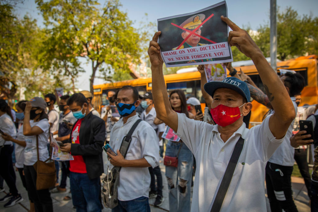 Myanmar protesters hold photos of General Min Aung Hlaing while calling for the end of the Myanmar military coup outside the United Nations headquarters for Southeast Asia on February 03, 2021 in Bangkok, Thailand