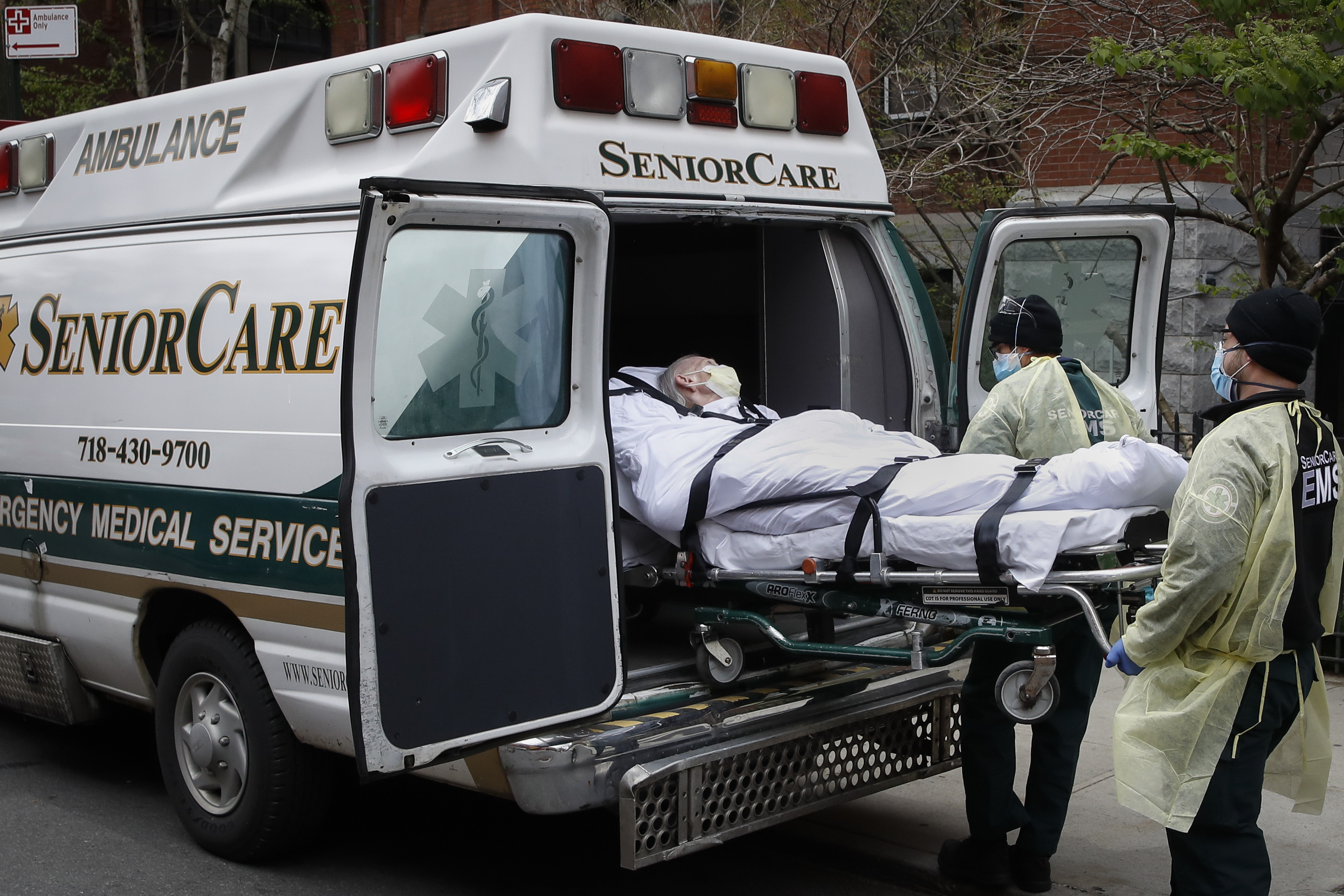 In this April 17, 2020, file photo, a patient is loaded into an ambulance by emergency medical workers outside Cobble Hill Health Center in the Brooklyn borough of New York. More than 9,000 recovering coronavirus patients in New York state were released from hospitals into nursing homes at the height of the pandemic under a controversial order that was scrapped amid criticisms it accelerated outbreaks, according to new records obtained by The Associated Press.