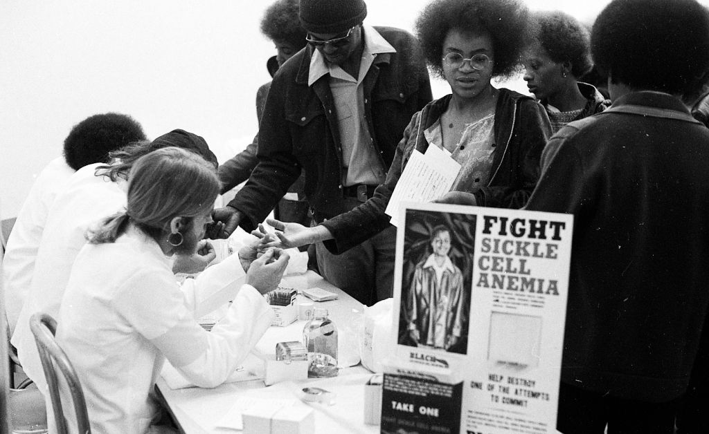 Black Panthers put on a Black Community Survival Conference at the Civic Auditorium in San Francisco in April 1972, where bags of groceries are given away, and participants can also take sickle cell anemia tests and register to vote.