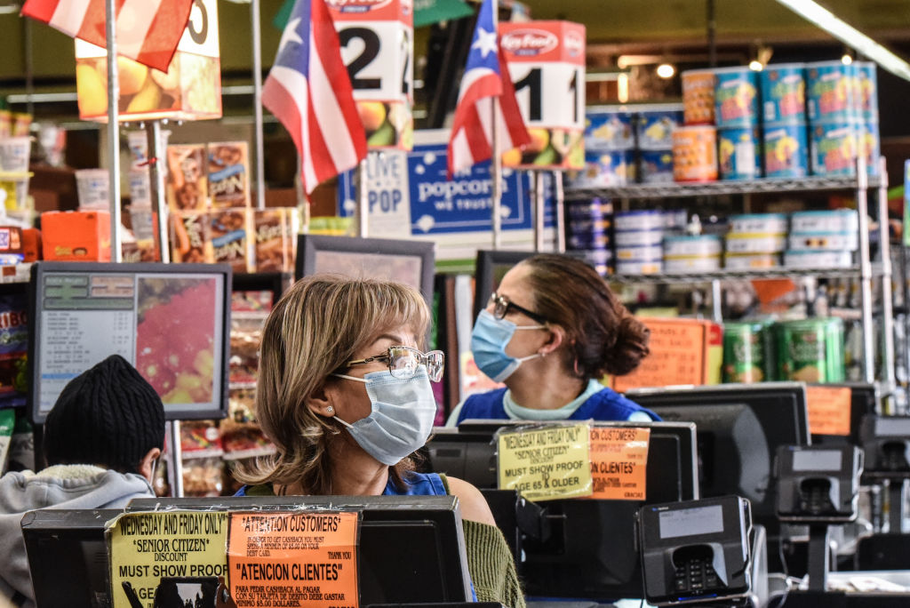 Cashiers wearing protective masks work in a grocery store in the Bushwick neighborhood of Brooklyn on April 2, 2020 in New York City.