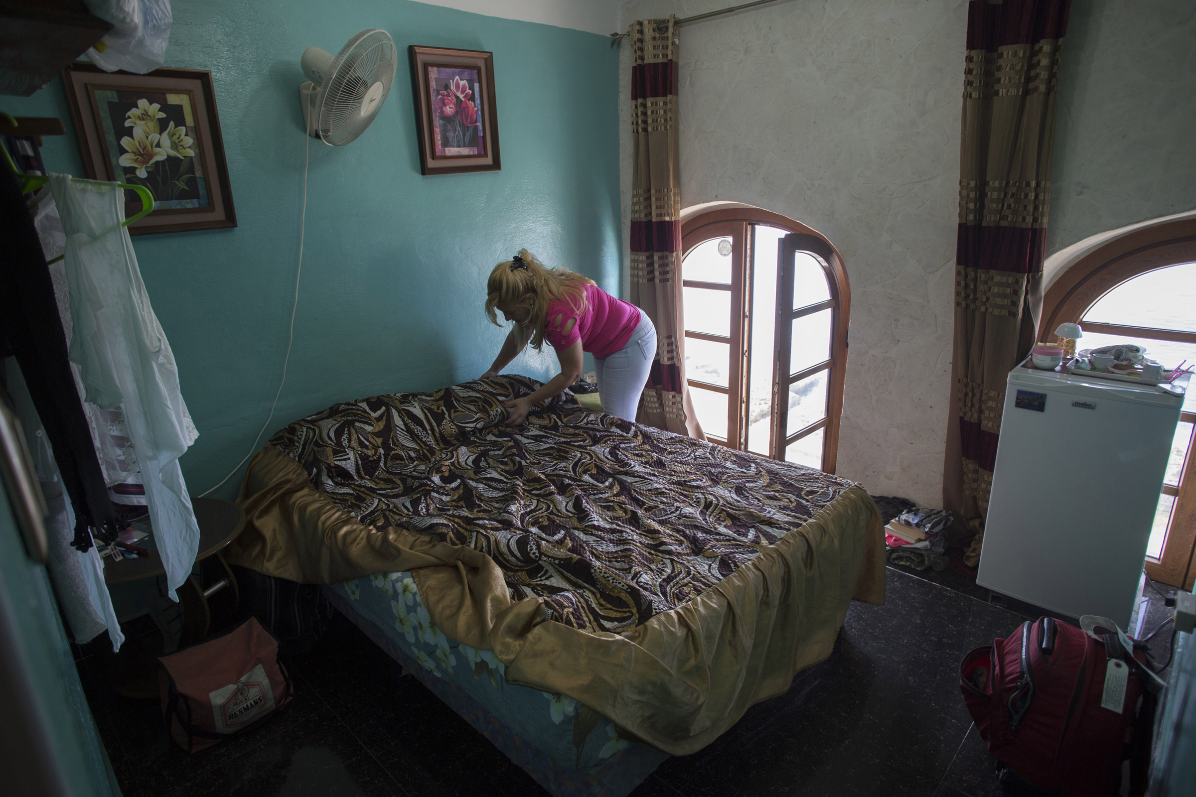Amarilis Placensia makes a bed at a home rented to tourists in Havana, on Jan. 11, 2020.