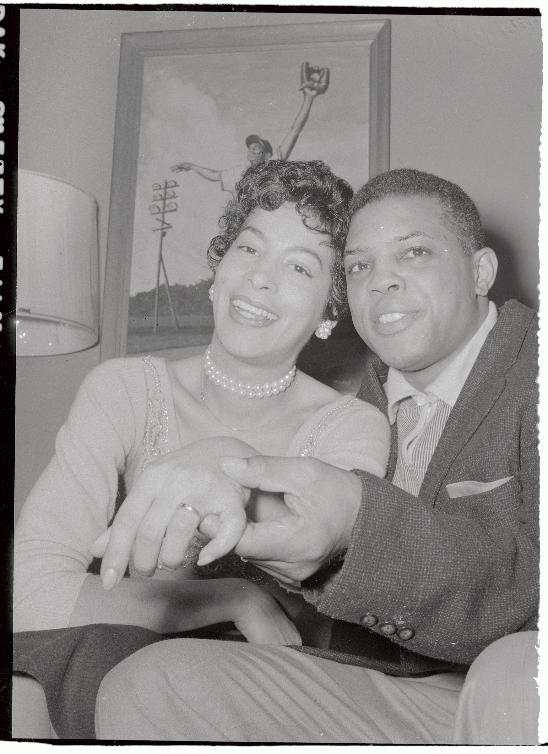 New York Giants star outfielder Willie Mays, 25, is shown with his bride of a few hours, Marguerite Wendelle, 27, at her home in Elmhurst, N.Y. after their wedding in Elkton, Md. on Feb. 14, 1956. En route to Elkton, Mays was arrested for driving 70 miles an hour on the New Jersey turnpike and paid a $15 fine.