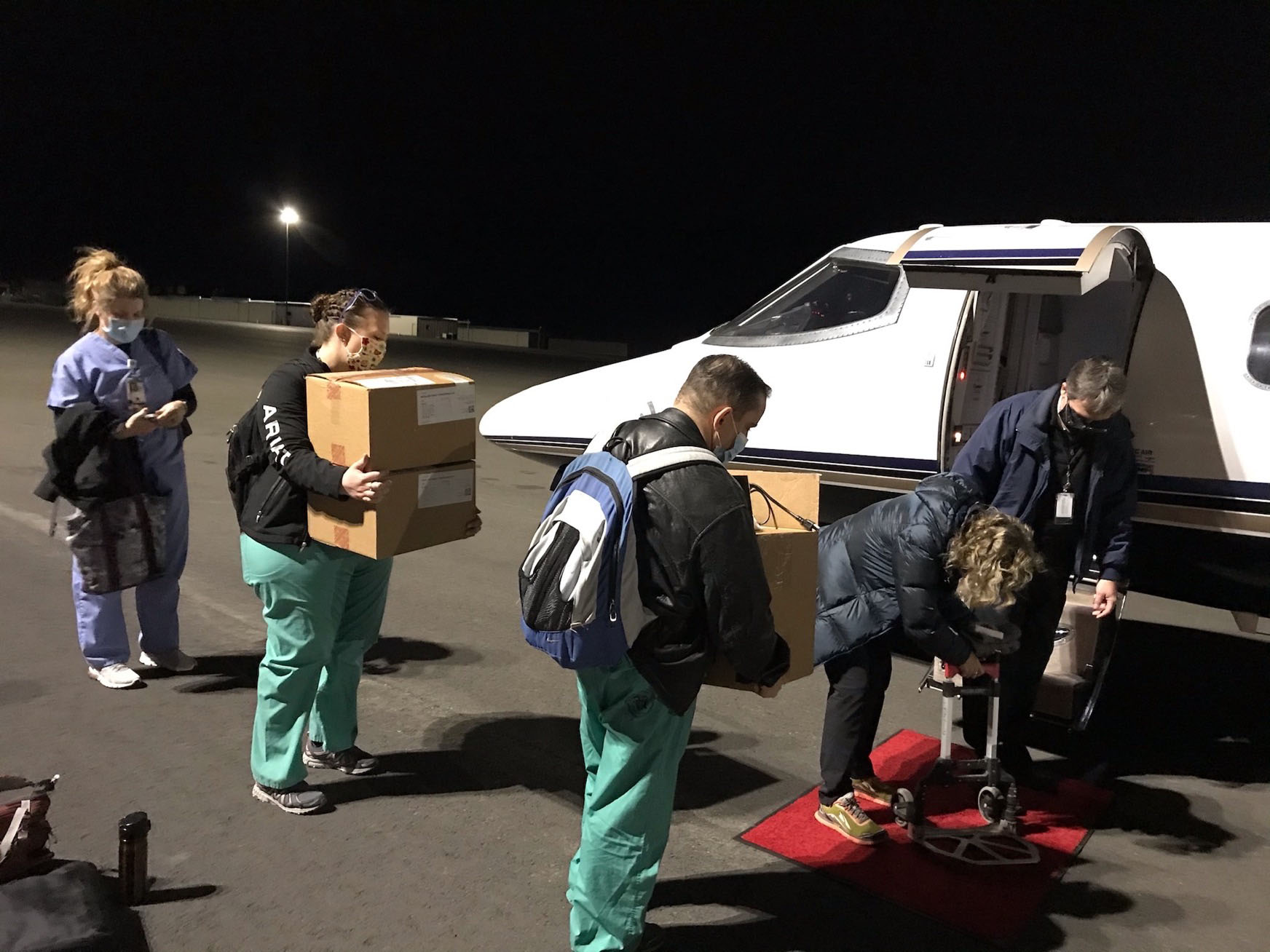 A vaccination team bound for Havre, Mont., loads supplies for transporting the Moderna vaccine into a plane at the Helena Regional Airport. Also on board were six Veterans Affairs providers tasked with inoculating rural veterans with the COVID-19 vaccine.