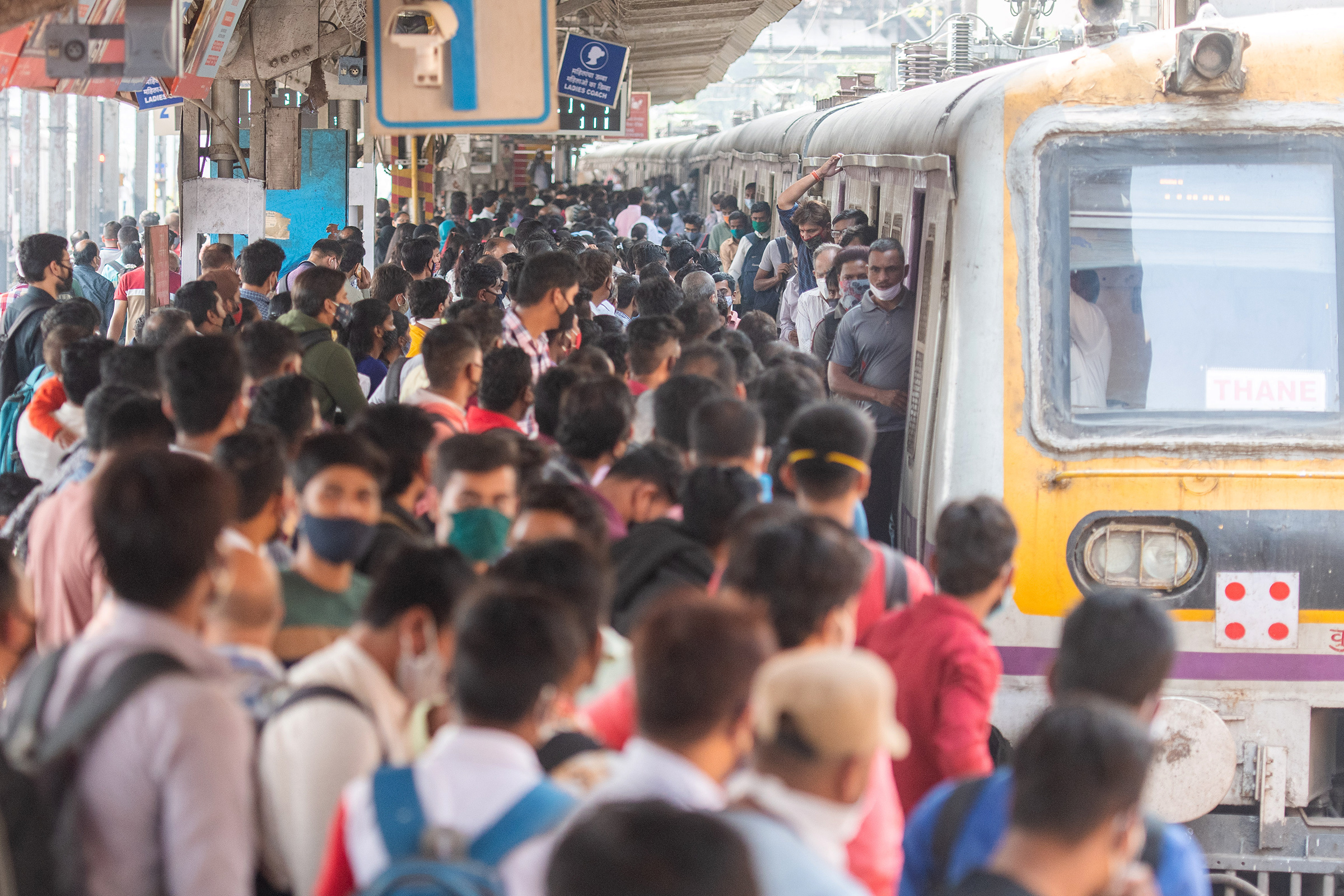 A rush of travellers wait to board a suburban local train at Dadar station, Mumbai, on the first day when local train services started for the general public on Feb 1.
