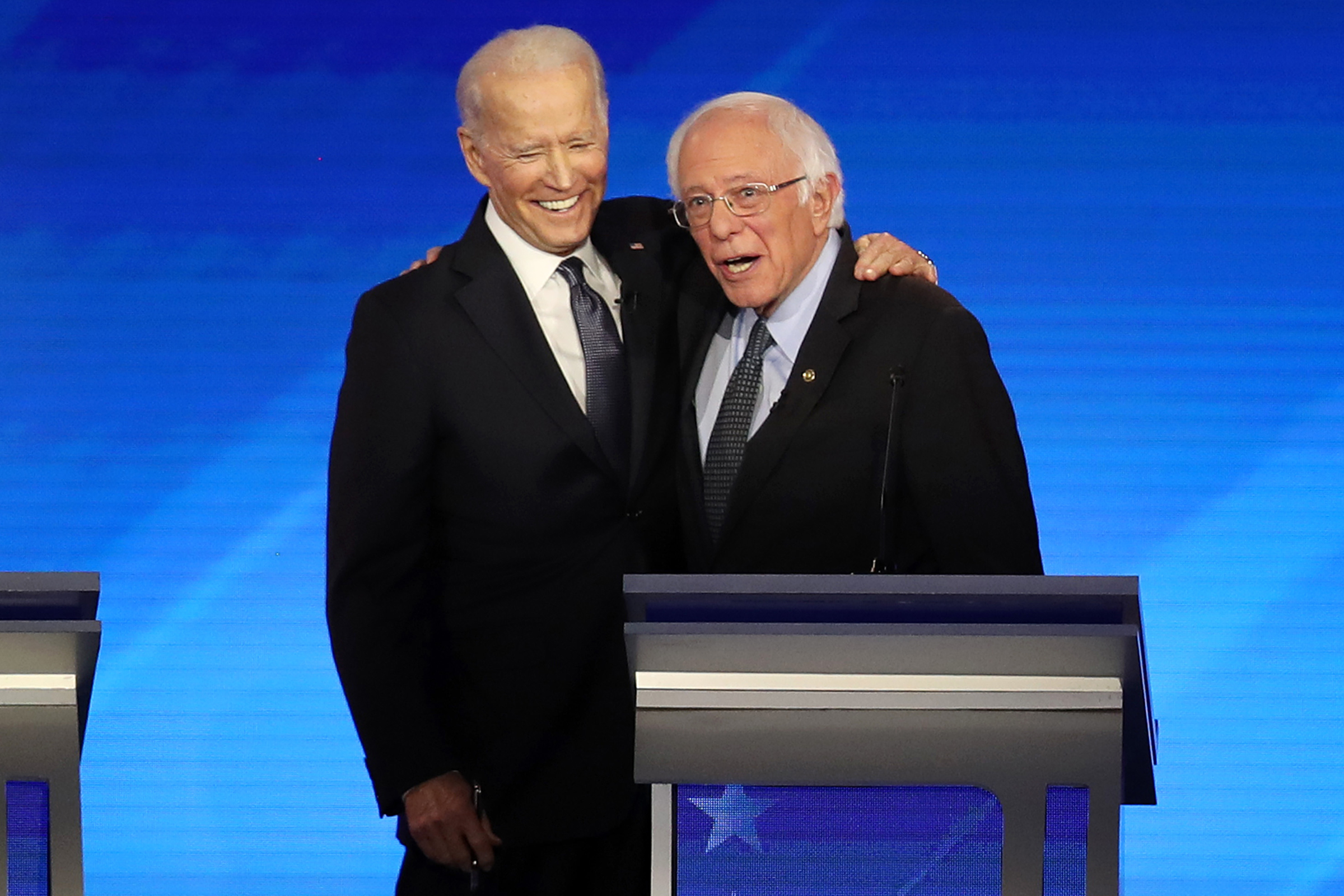 Then-presidential candidates Joe Biden and Sen. Bernie Sanders share a moment during the Democratic presidential primary debate in Manchester, N.H. on Feb. 7, 2020.