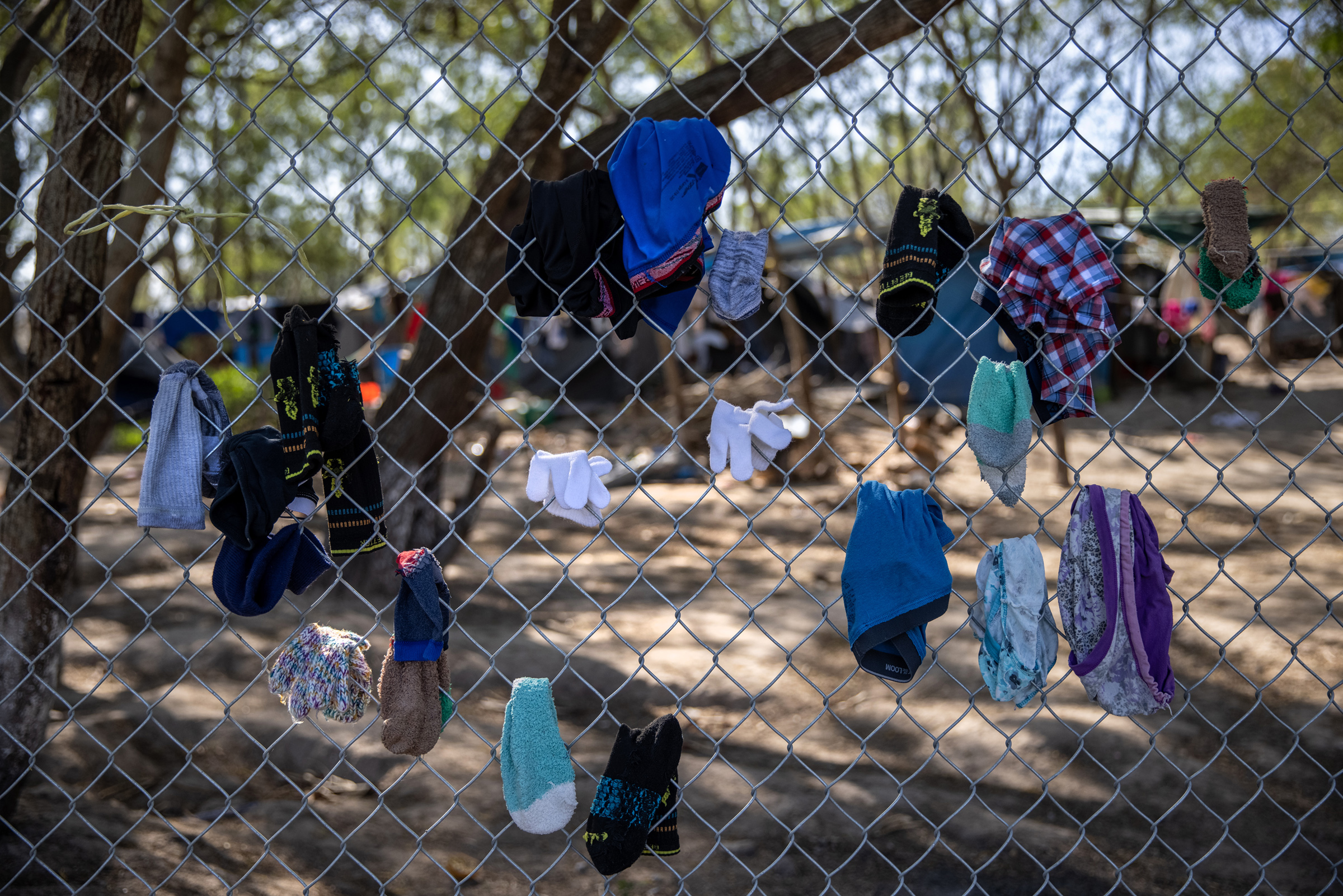 Clothing drying on a fence at a camp for asylum seekers in Matamoros, Mexico, on Feb. 7, 2021.