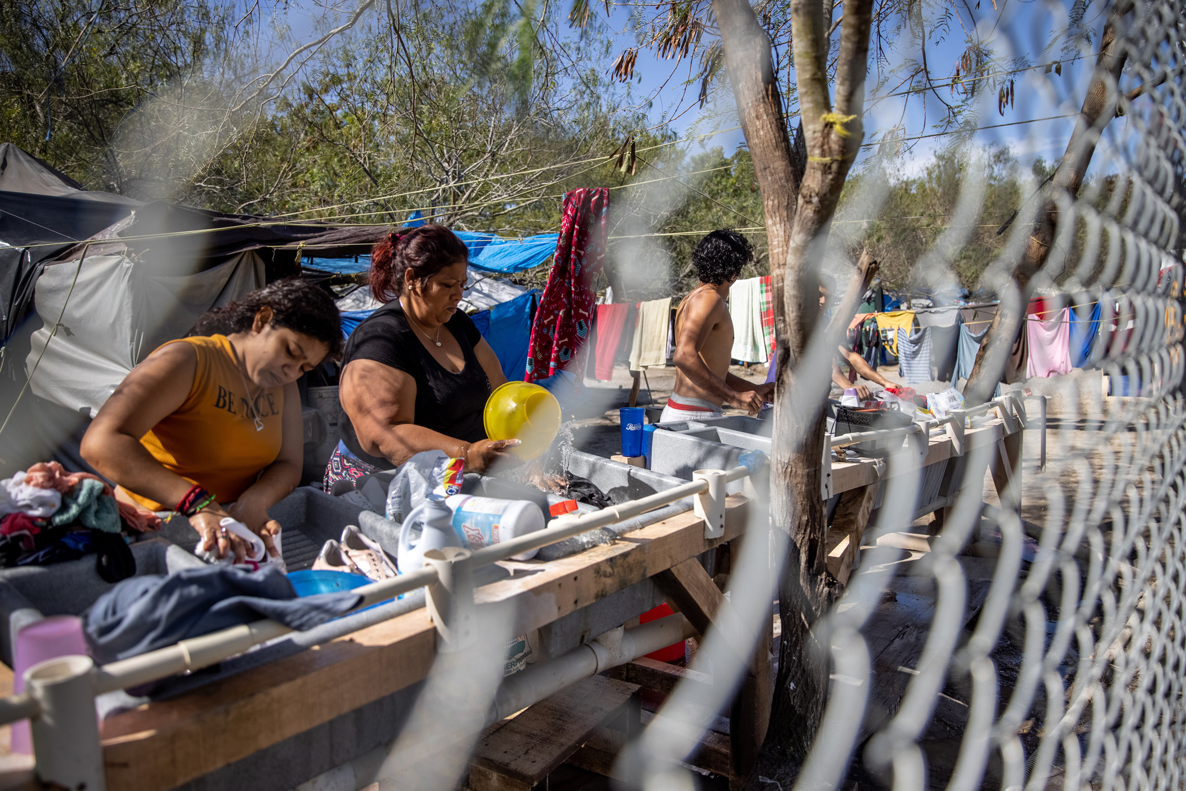 Asylum seekers washing clothing inside a camp in Matamoros, Mexico on Feb. 7, 2021.