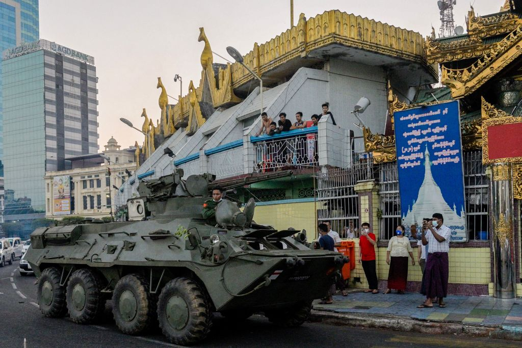 An armored vehicle drives next to the Sule Pagoda, following days of mass protests against the military coup, in Yangon on Feb. 14, 2021.