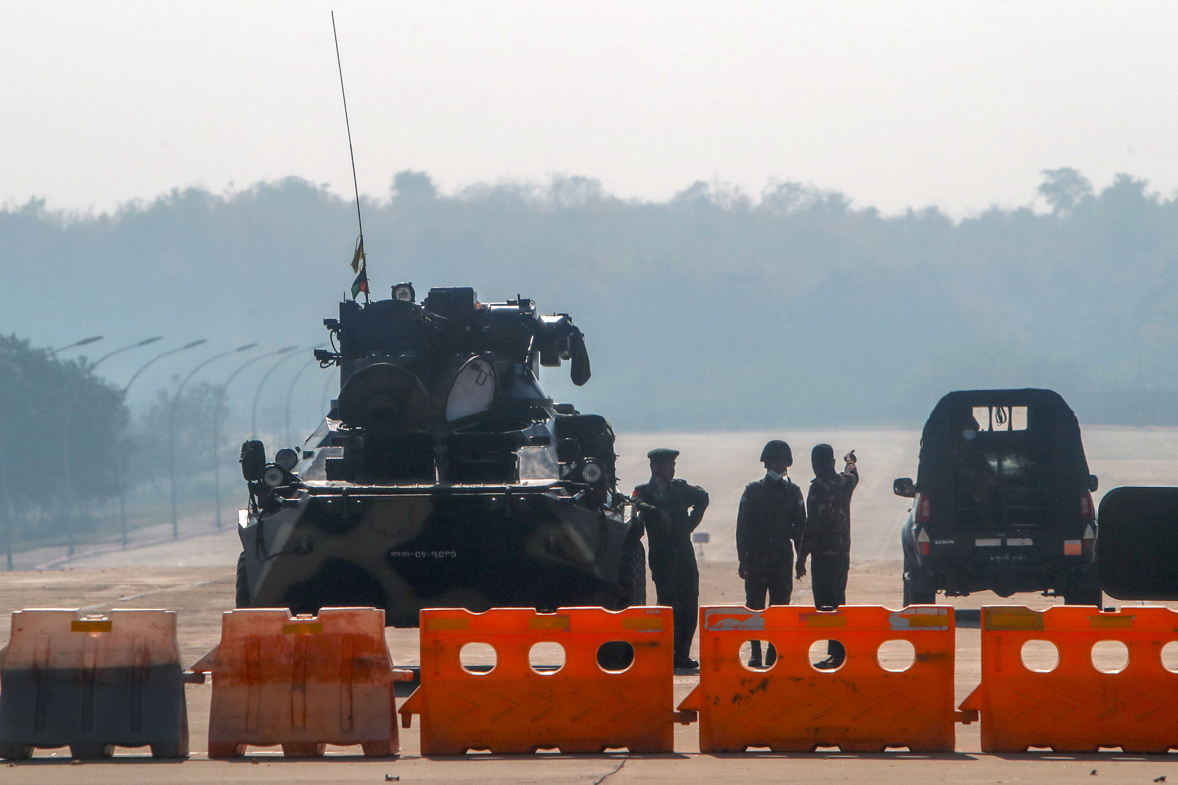 Myanmar's military stand guard at a checkpoint manned with an armored vehicle in a road leading to the parliament building Tuesday, Feb. 2, 2021, in Naypyitaw, Myanmar.