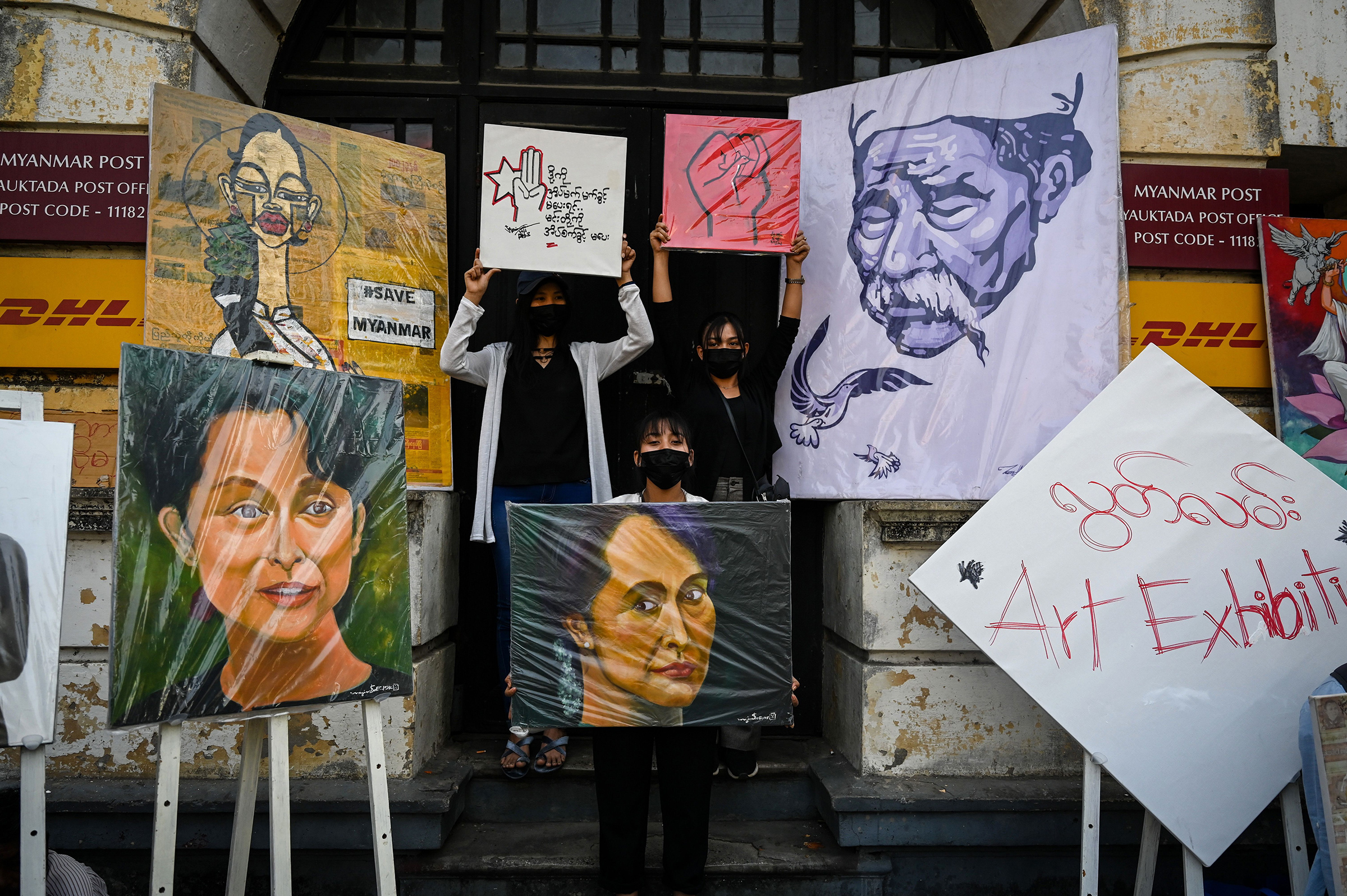 Protesters stand next to portraits of Aung San Suu Kyi and other artwork during a demonstration against the military coup in Yangon on Feb. 9