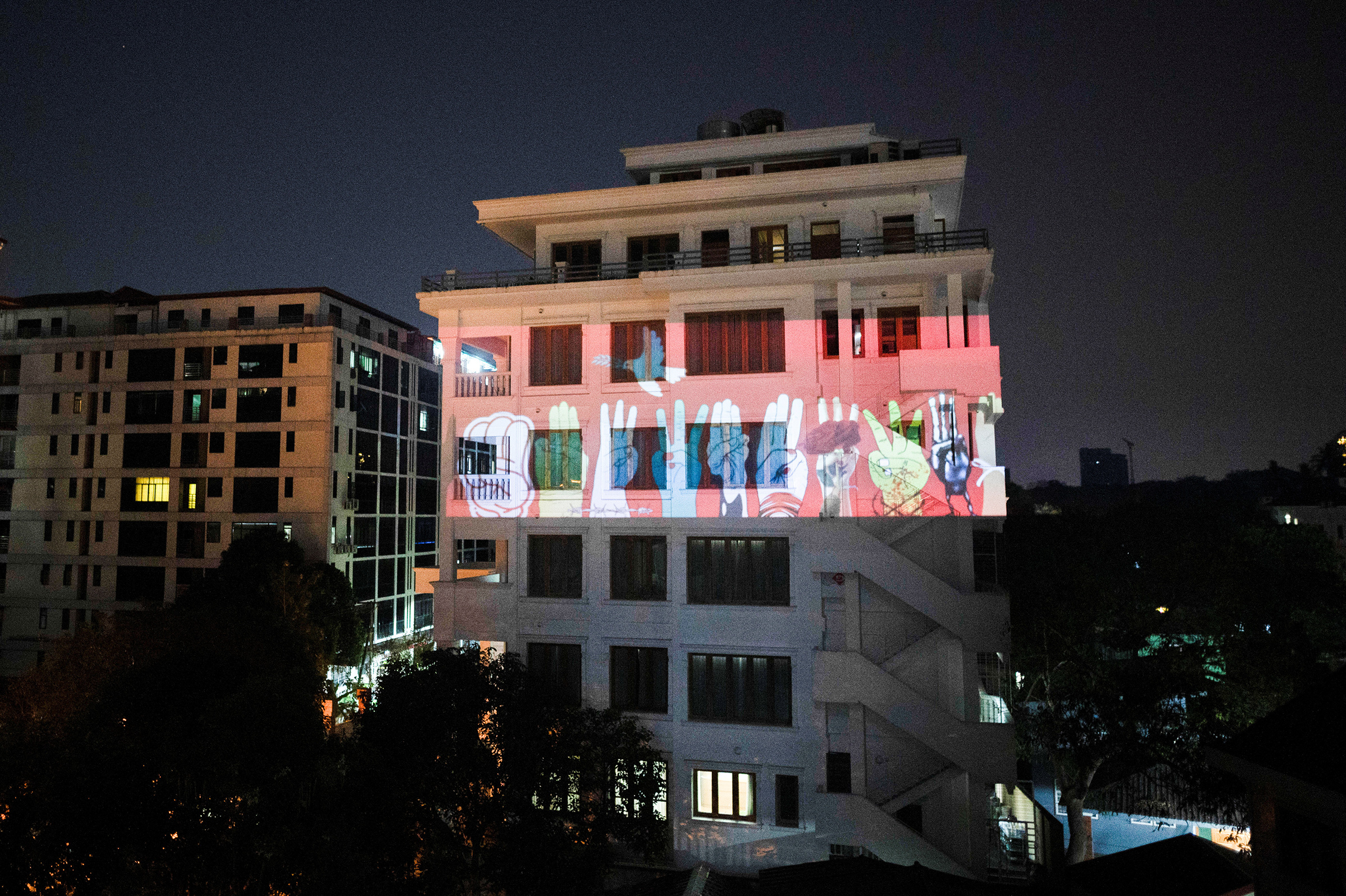 An image of three-finger salute is projected on a building during a night protest against the military coup and to demand the release of elected leader Aung San Suu Kyi, in Yangon, Myanmar, Feb. 9