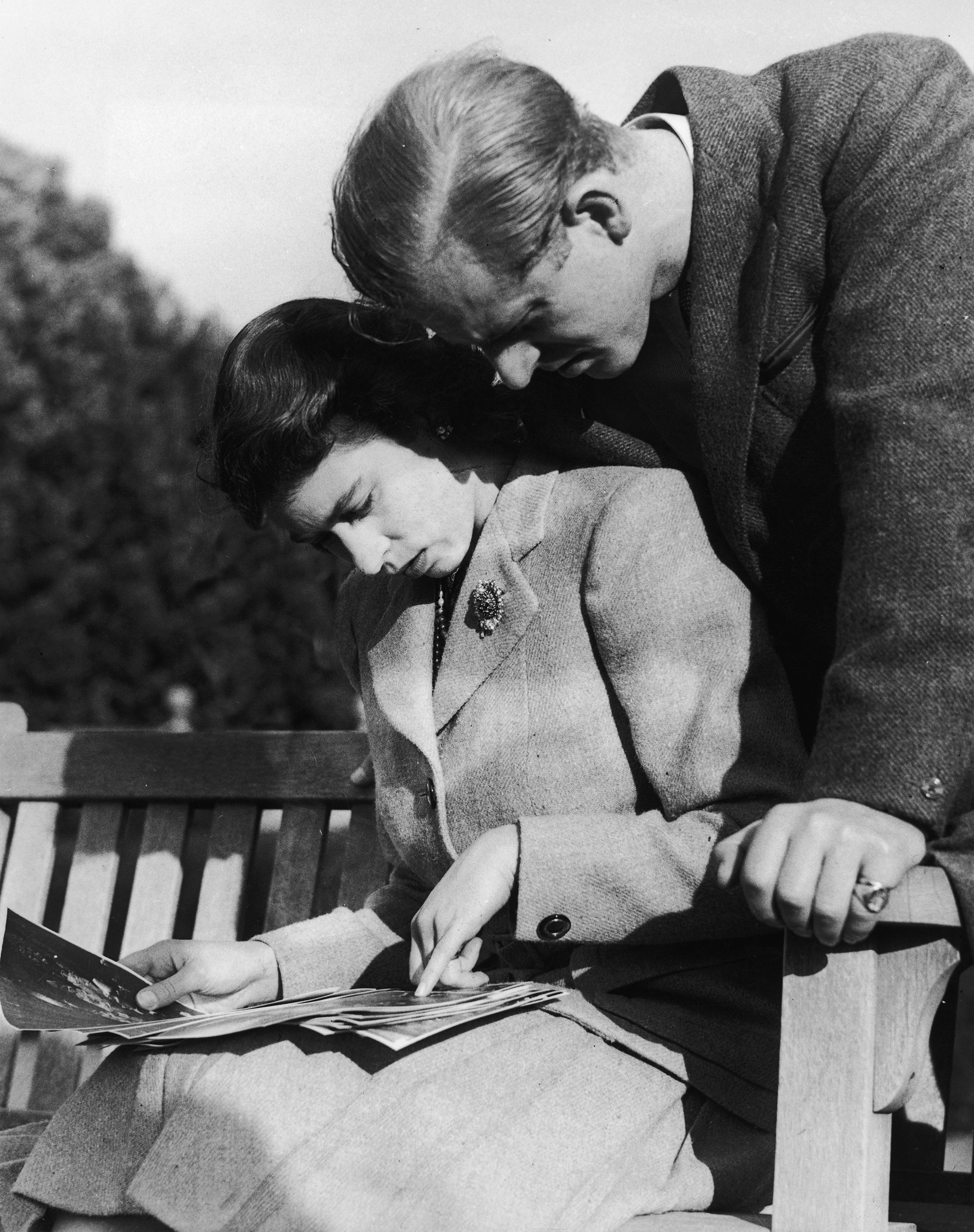 Princess Elizabeth and Philip Mountbatten, Duke of Edinburgh, look at their wedding photographs while on honeymoon in Romsey, Hampshire, Nov. 1947.