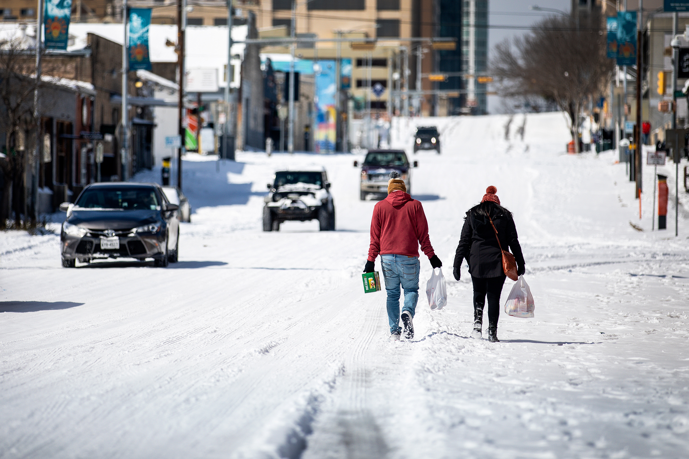 People carry groceries on Feb.15 in Austin after a winter storm brought historic cold weather to Texas