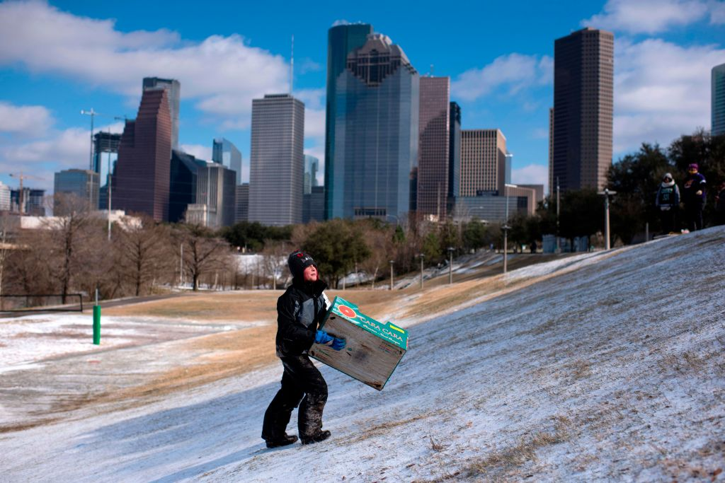 A boy walks up a snow covered hill after sledding down it in a box in Houston, Texas on Feb. 15, 2021. Much of the United States was in the icy grip of an  unprecedented  winter storm on Feb. 15, with as many as 5 million Americans losing power.