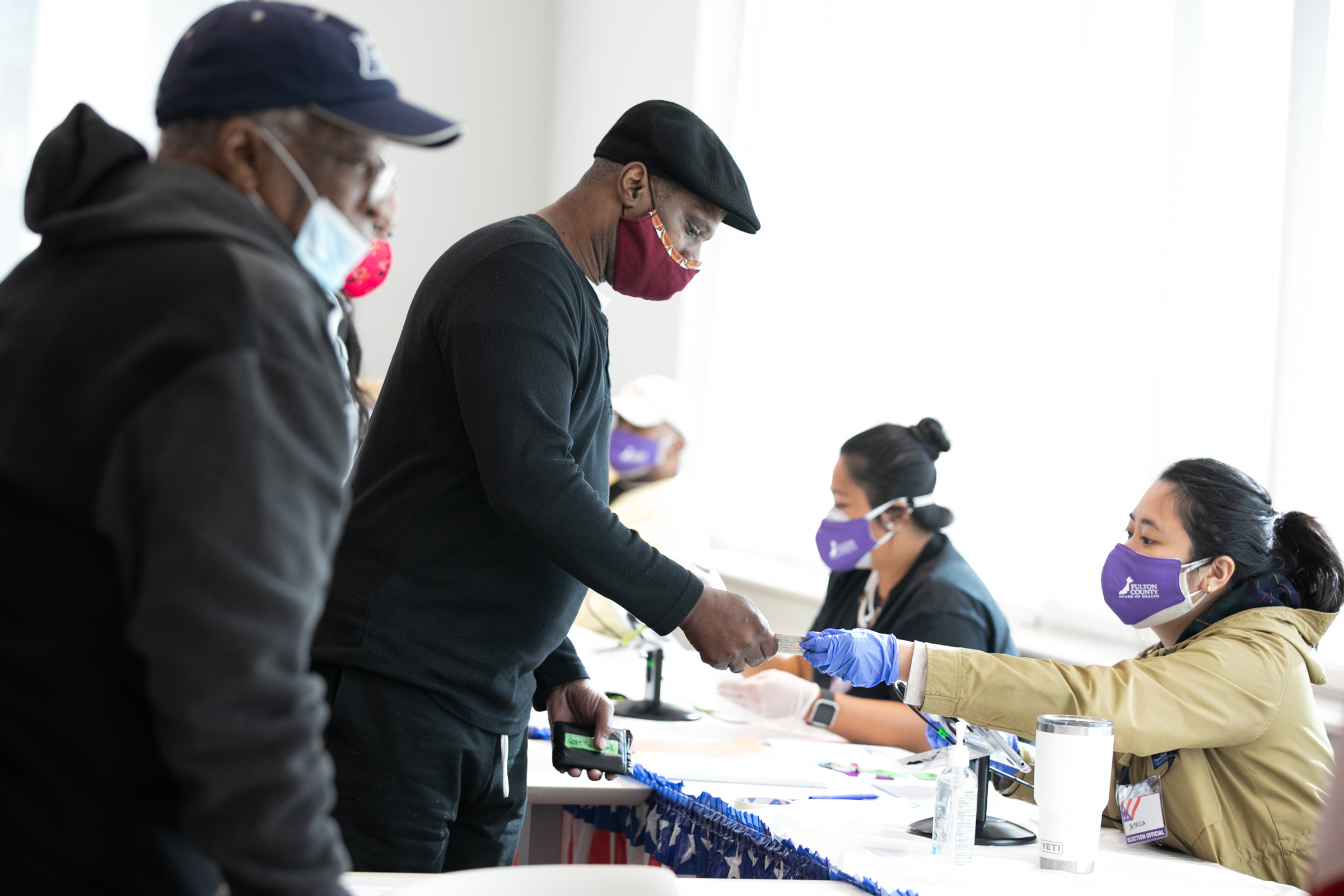 Voters check-in with poll workers to cast their ballots in Atlanta on Nov. 3, 2020.