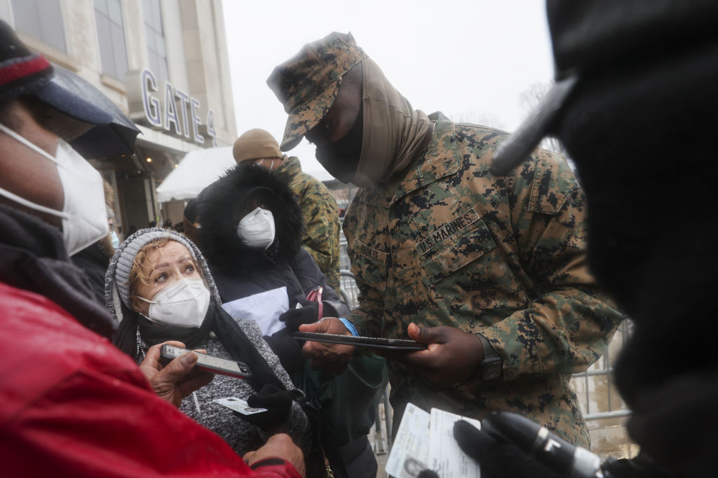 A member of the U.S. Marines registers people wearing protective masks outside a COVID-19 vaccination hub inside Yankee Stadium in the Bronx borough of New York, U.S., on Feb. 5, 2021.