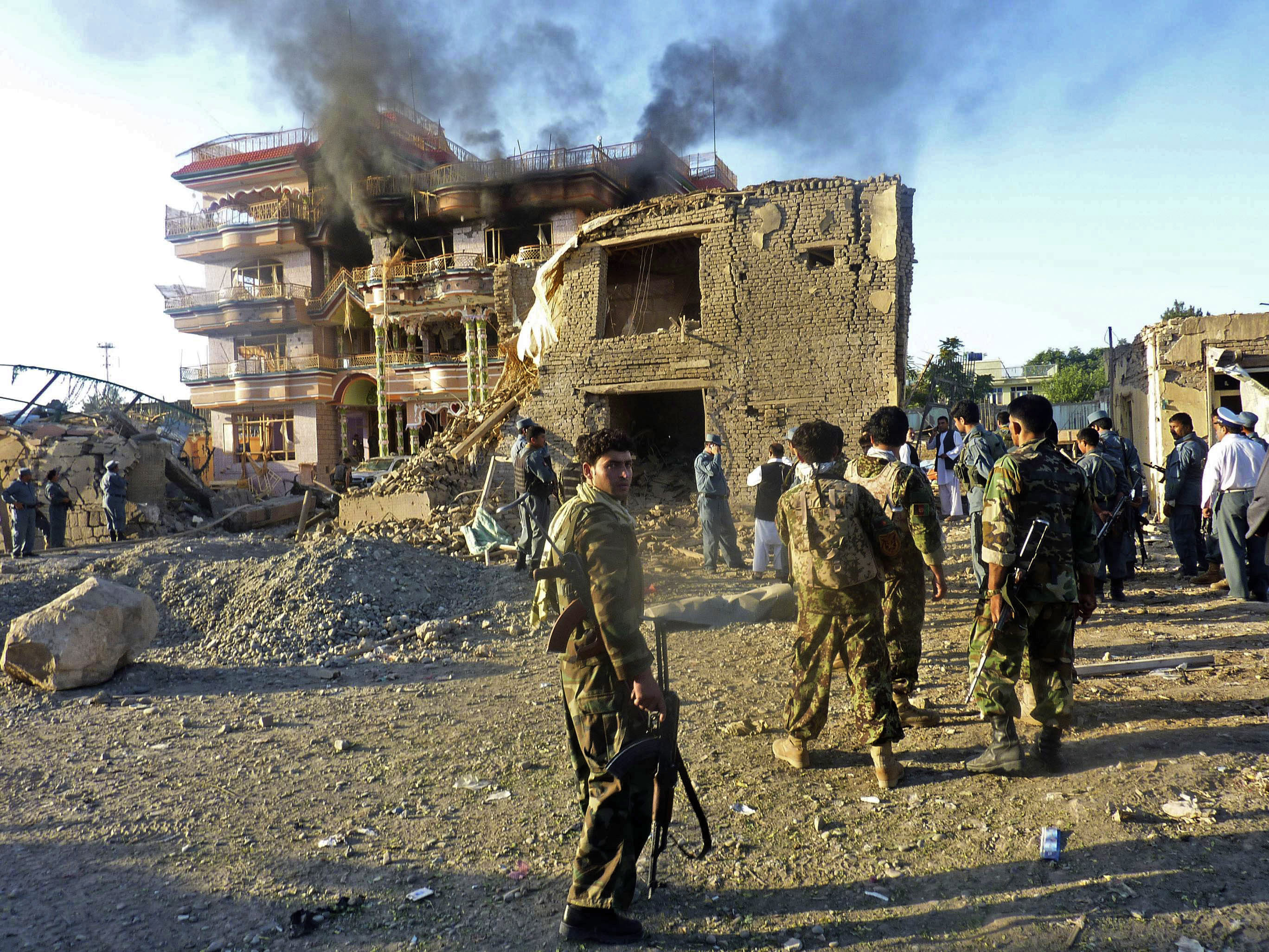 In this July 2, 2010 file photo, Afghan security forces stand outside a USAID compound in Kunduz, northern Afghanistan, after it was stormed by militants wearing suicide vests.