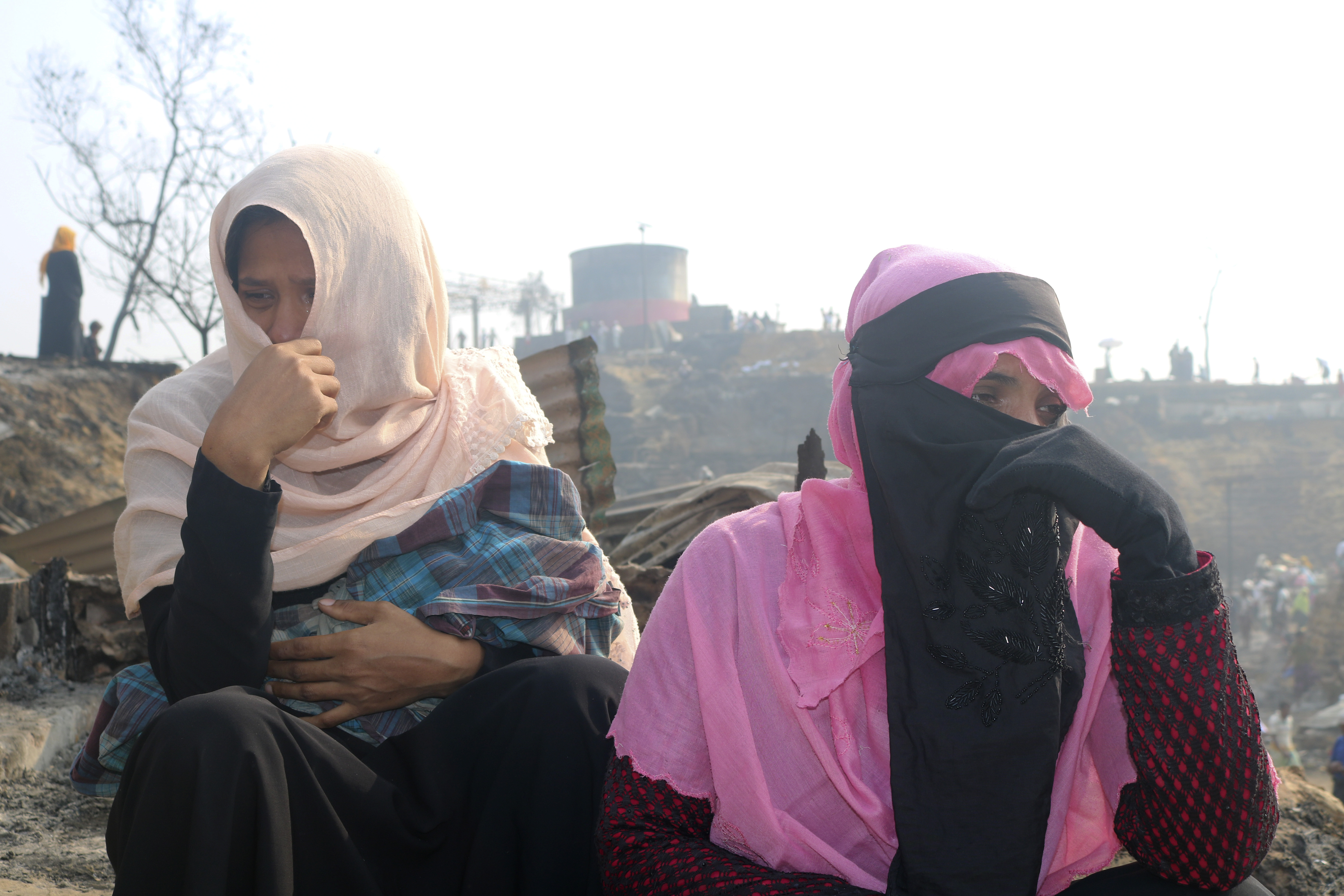 Rohingya refugees cry at the site of a fire at a refugee camp in Balukhali, southern Bangladesh, on Tuesday, March 23, 2021.