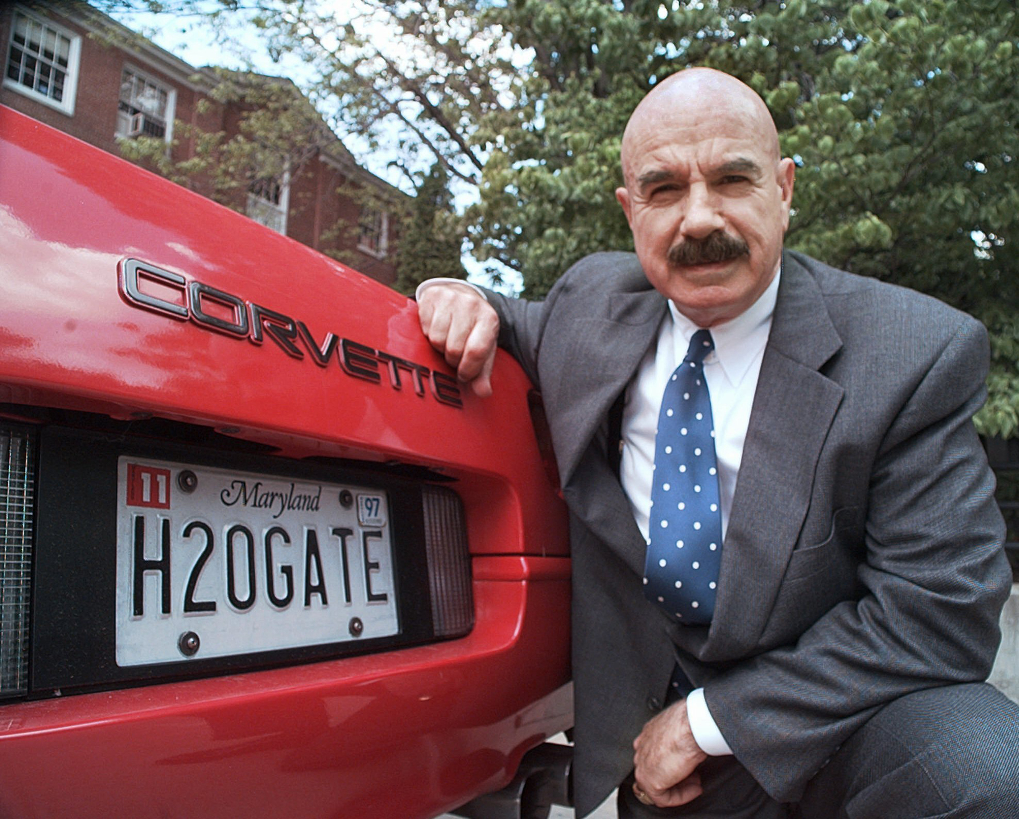 In this Monday, June 9, 1997, file photo, G. Gordon Liddy kneels next to his Corvette outside the Fairfax, Va., radio station where he broadcasts his syndicated radio talk show.