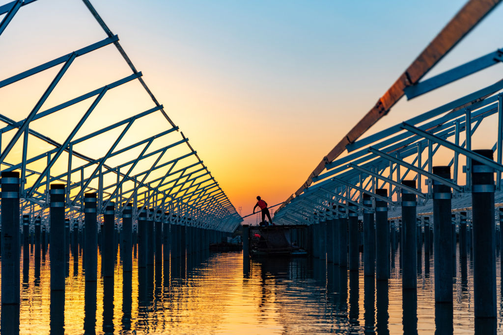 Workers at the construction site of a reservoir fishing and photovoltaic power station project install photovoltaic panels on floating boats in Hefei, Anhui Province, China on March 4, 2021.