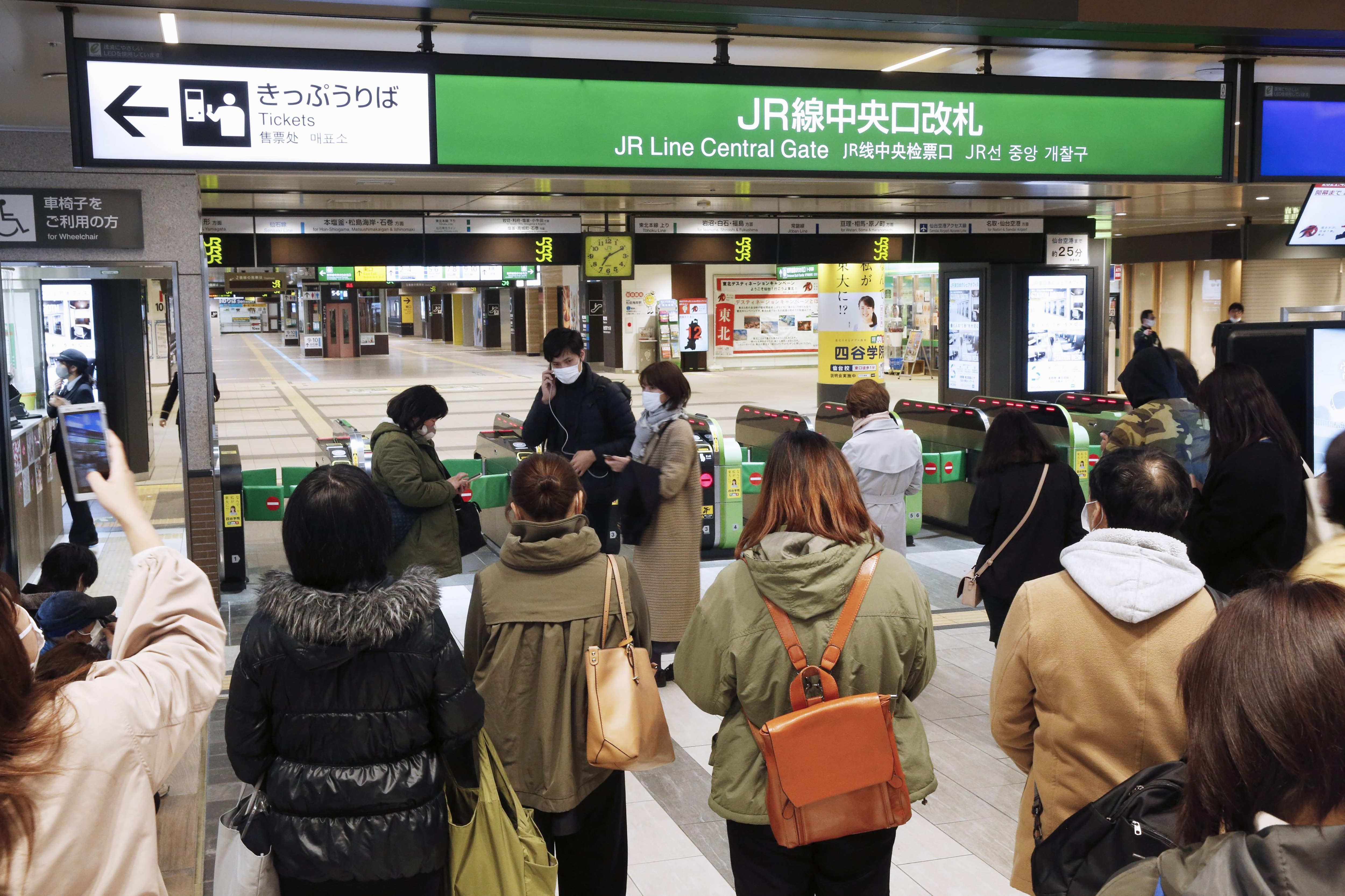 People gather in front of a ticket gate at a station as train services are suspended following an earthquake in Sendai, Miyagi prefecture, Japan, on March 20, 2021.