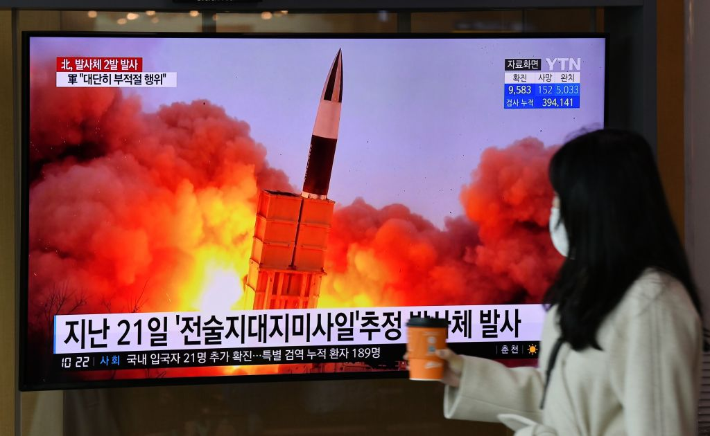 A woman walks past a screen showing file footage of a North Korean missile test, at a railway station in Seoul on March 29, 2020.