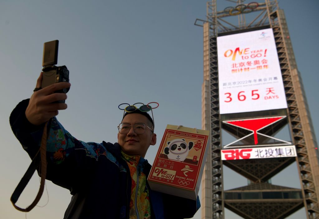 A man takes a selfie in front of a screen showing the remaining days till the 2022 Winter Olympics near the Birds Nest stadium, the venue for opening and closing ceremonies, in Beijing on February 4, 2021.