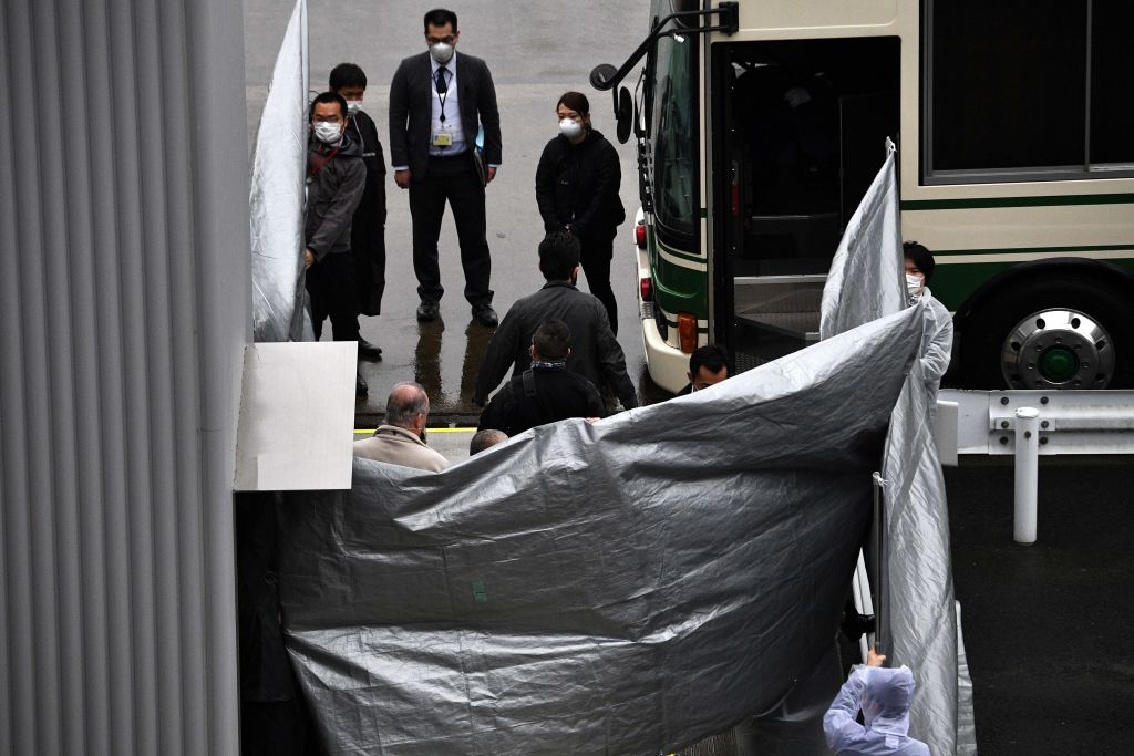 Japanese officials hold up plastic covers as a group of passengers get on a bus from the plane believed to be carrying former US special forces member Michael Taylor and his son Peter who allegedly staged the operation to help fly former Nissan chief Carlos Ghosn out of Japan in 2019, at Narita airport in Chiba prefecture on March 2, 2021.