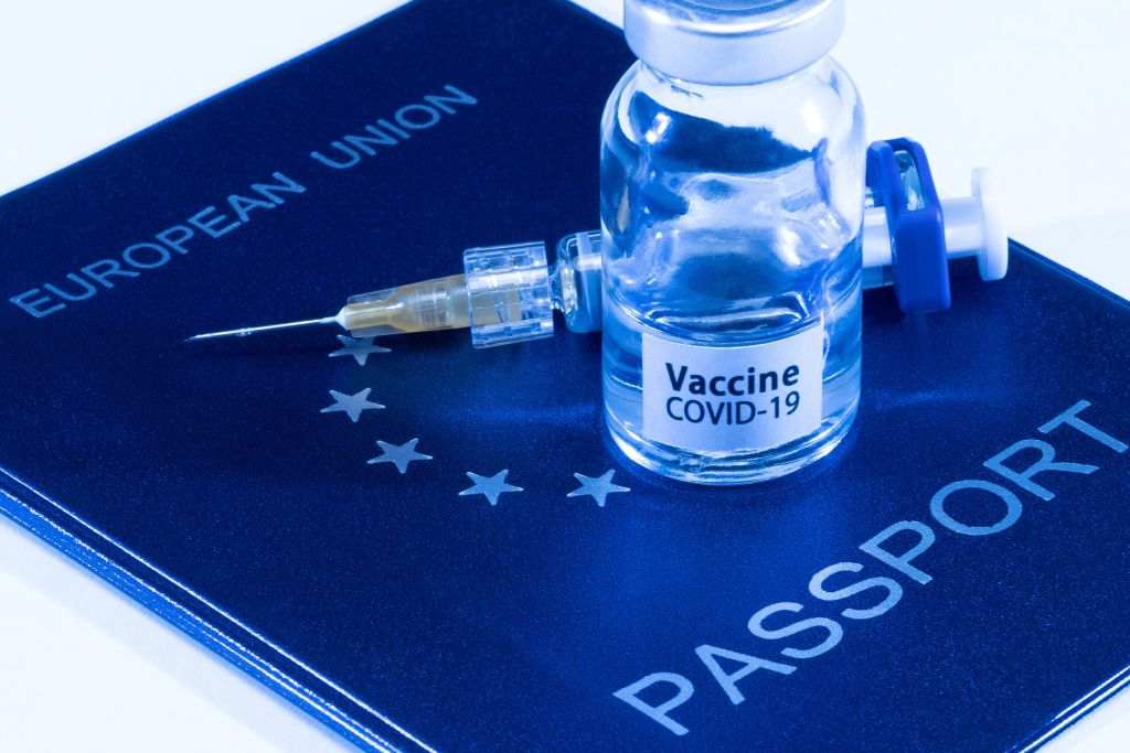 A picture taken on March 3, 2021 in Paris shows a vaccine vial reading  Covid-19 vaccine  and a syringe on an European passport.