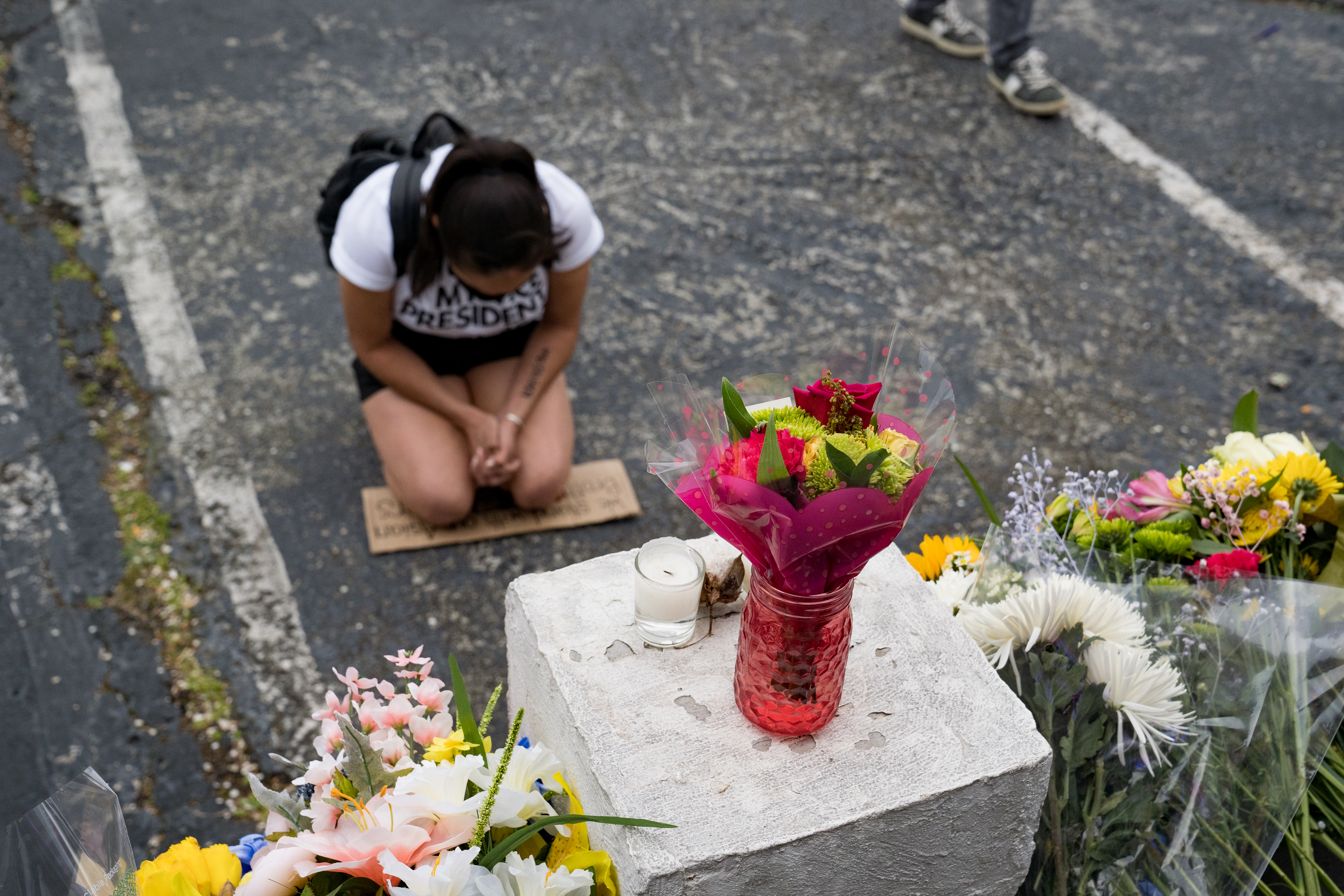 A woman kneels at a memorial outside the Gold Spa in Atlanta on March 18, one of three spas attacked by a gunman who killed eight the previous day