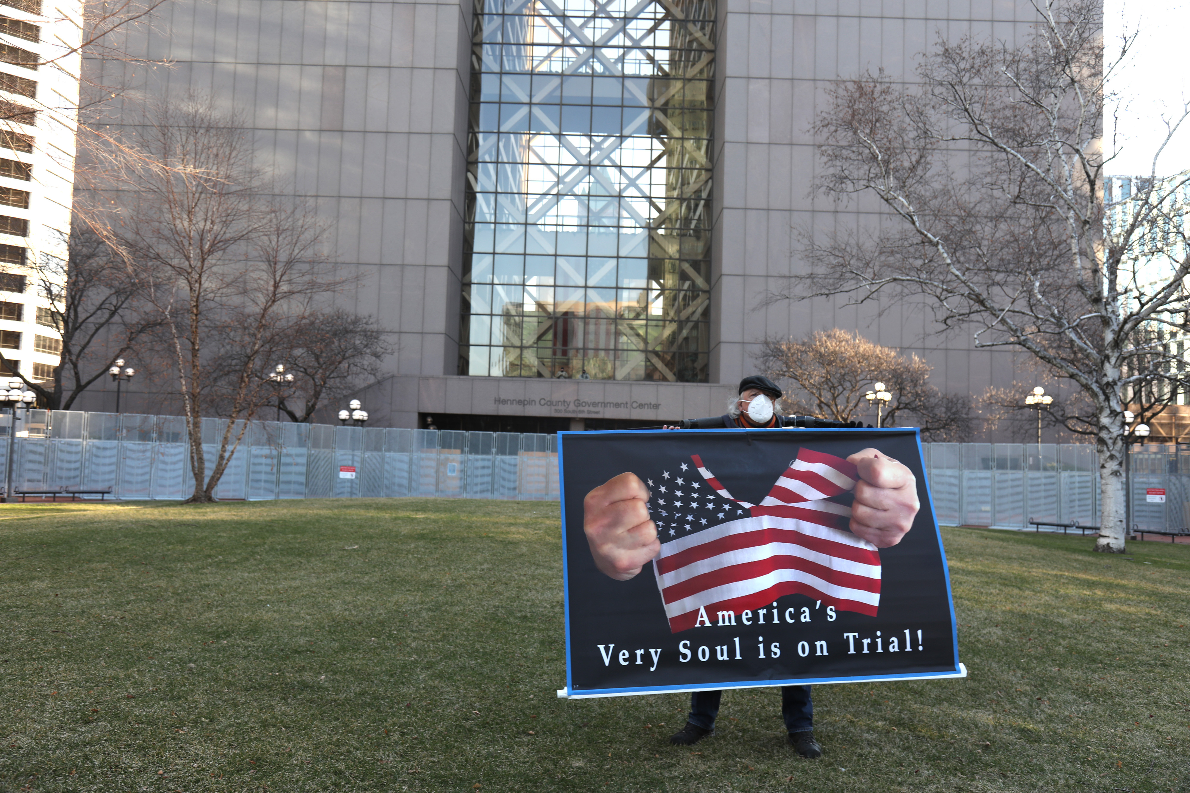 A demonstrator holds a sign outside the Hennepin County Government Center in Minneapolis on Monday, March 29, 2021., as Derek Chauvin's trial began in a courtroom inside