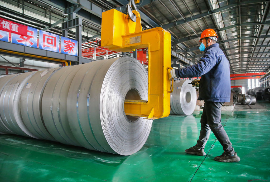 A worker transfers steel coils at a factory of Lianyungang Huale Alloy Group CO., LTD on February 24, 2021 in Lianyungang, Jiangsu Province of China.