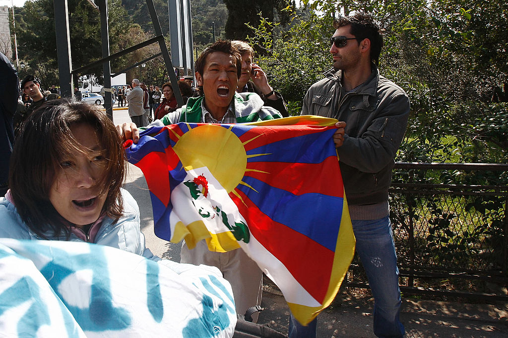 Pro-Tibetan demonstrators, holding a tibetan flag, are detained by plain clothes Greek policemen as they protest and shout anti-Chinese slogans during the handover ceremony of the Olympic flame to China on March 30, 2008 outside the Panathinaiko stadium in Athens.