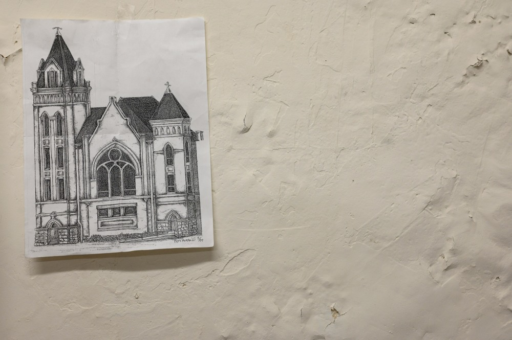 """A drawing by Ron hangs in the makeshift office of """"Street Mom†Susan Brossman in the basement of Youth Social Services, March 16, 2020. The drawing was given to Susan by Ron, who is unhoused in Wheeling, WV. Ron drew this image of a church that he could see from his window at a crisis unit for detox. Ron has been in the crisis unit over twenty times."""