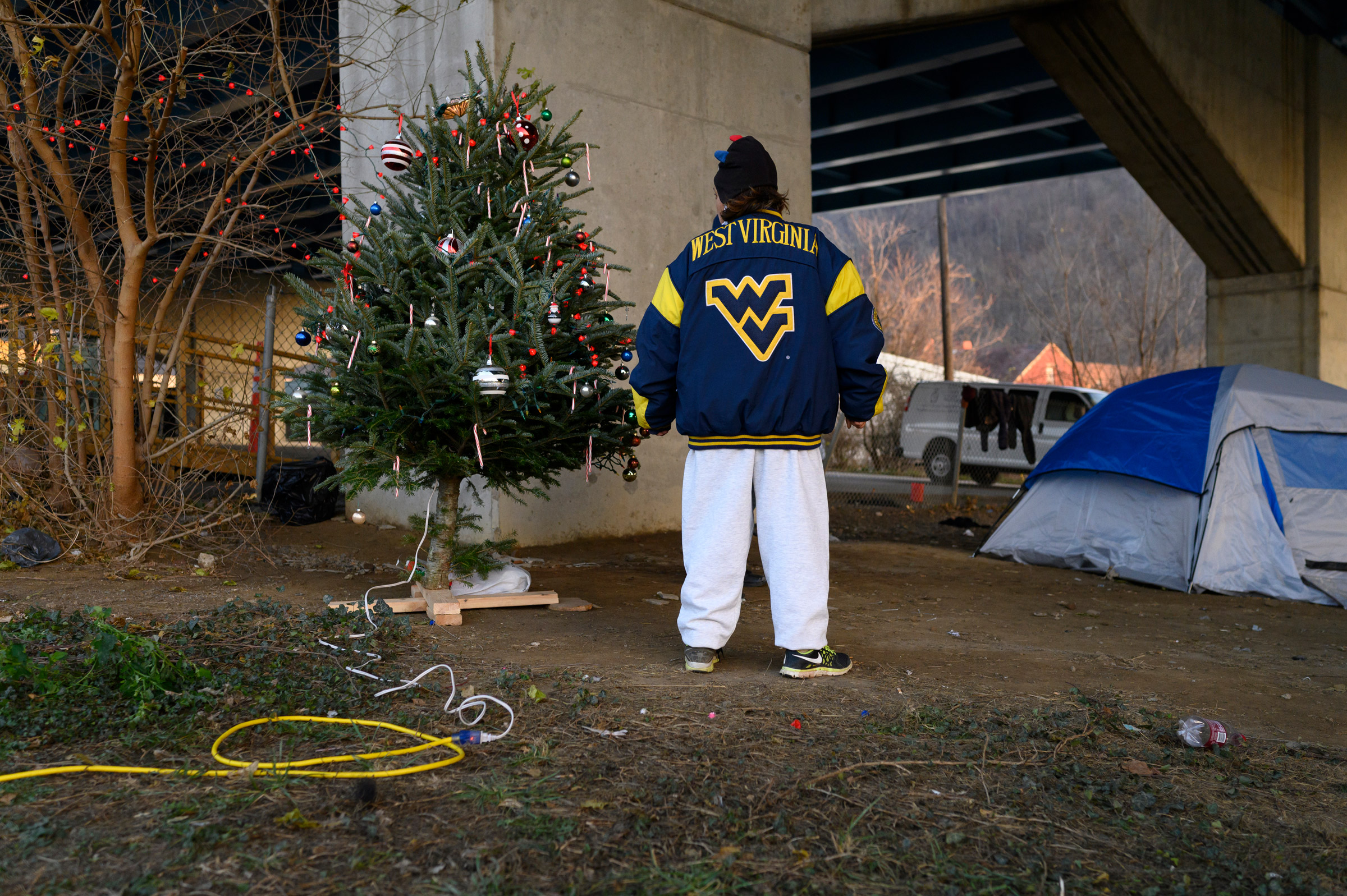 Chrissy stands by a Christmas tree in her encampment on Dec. 9. Chrissy helped bring the tree with others to hold a celebration and sing carols. After complaints, the City of Wheeling removed the tree's power, citing that they agreed to supply electricity for a temporary shower station adjacent to the camp but had not agreed to have it used for anything else.
