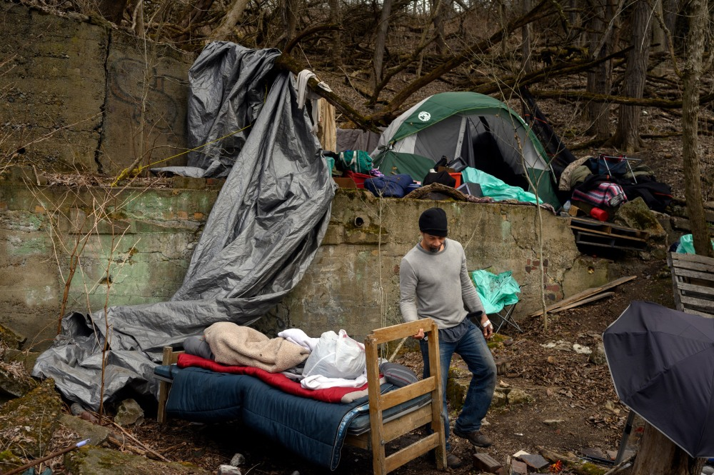 """A man who goes by the name """"Seven†builds up his tent encampment in Wheeling, WV on March 16, 2021. When the Winter Freeze shelter closed for the year, the unhoused population had to prepare to live outside for the remainder of the year."""
