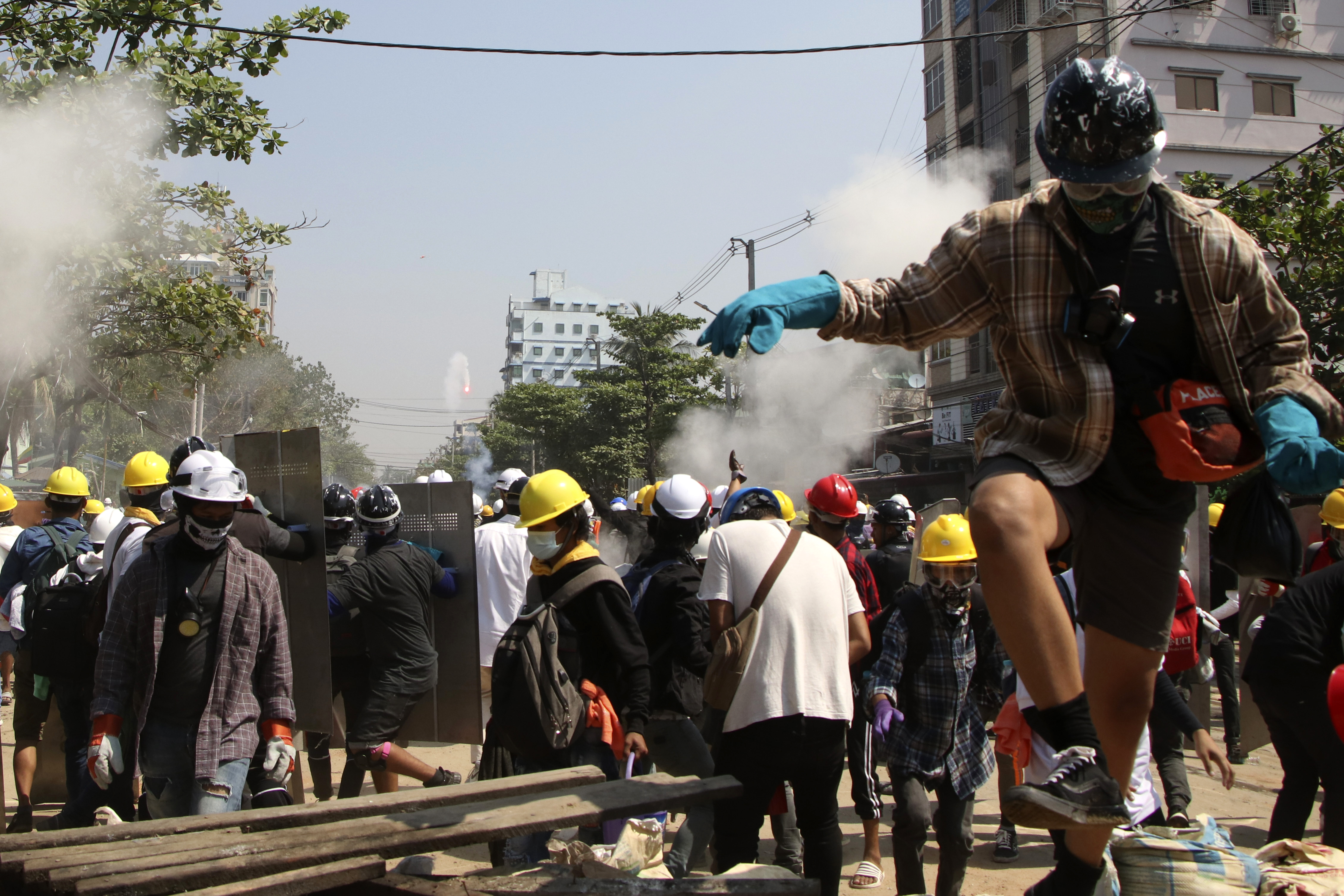 Protesters are dispersed as riot police fired tear gas behind a makeshift barricade in Yangon, Myanmar, on March 7, 2021.